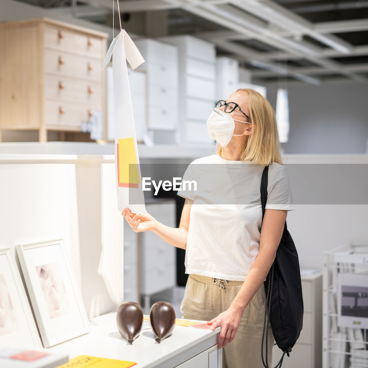 Side view of woman wearing mask standing at store