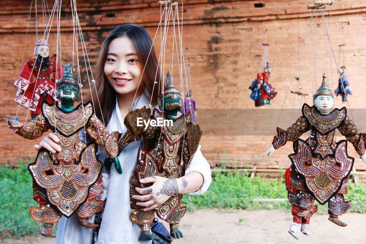 Portrait of smiling young woman holding puppets hanging outdoors