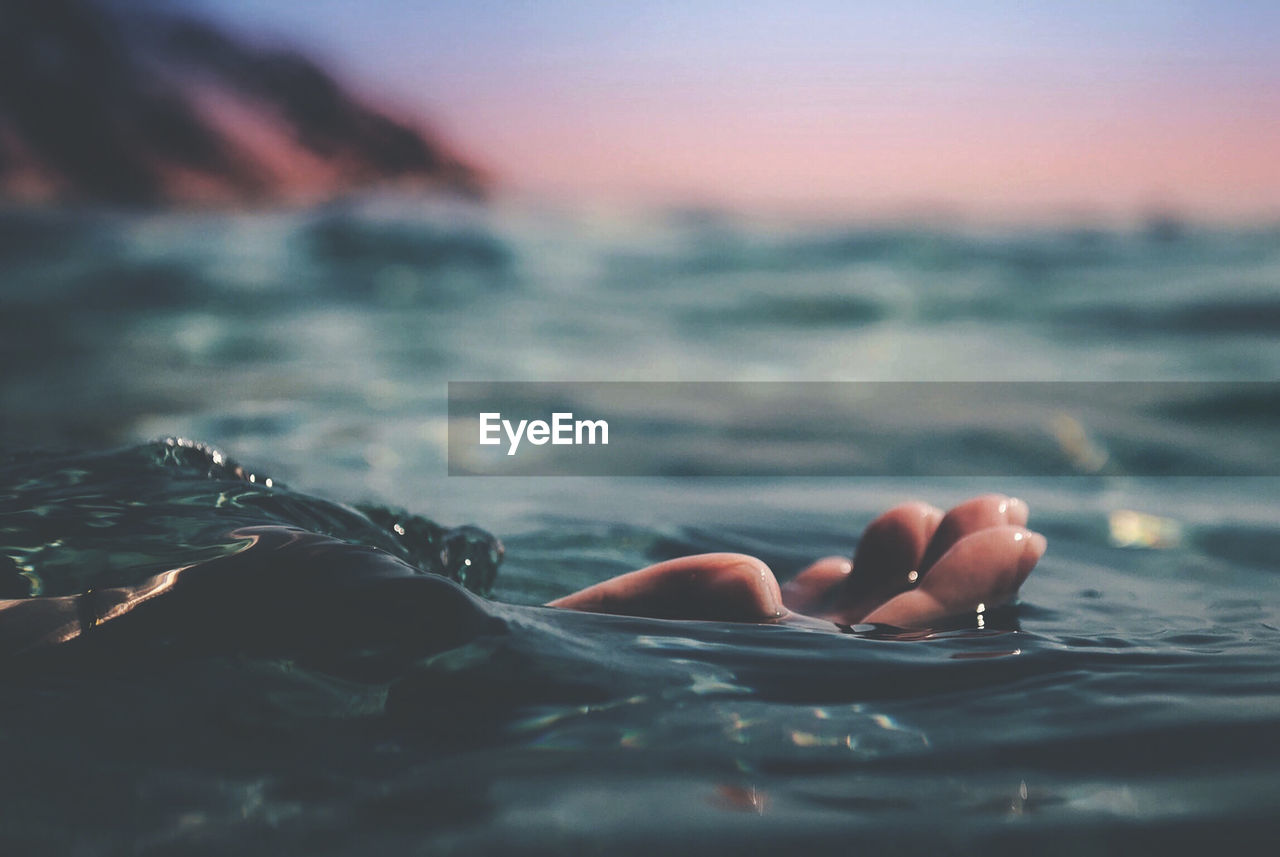 water, sea, human hand, hand, one person, human body part, nature, beauty in nature, sky, waterfront, sunset, tranquility, selective focus, day, outdoors, land, real people, scenics - nature, body part, finger