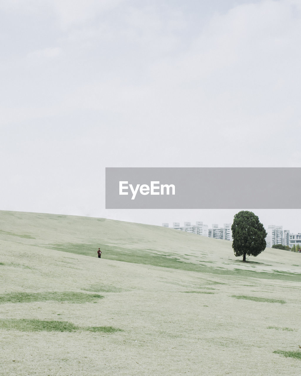 Distance view of person standing on hill against sky