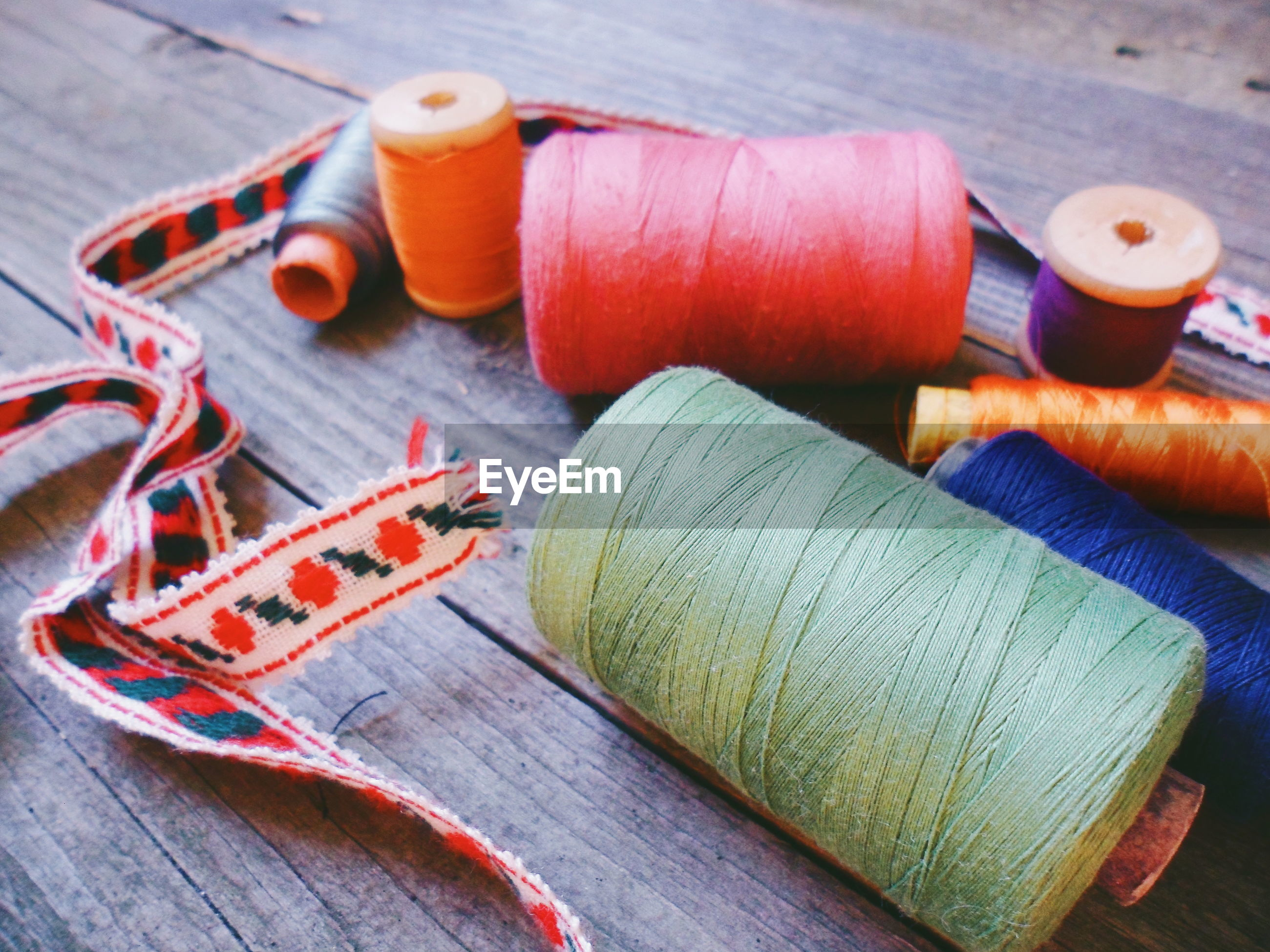 High angle view of multi colored thread spools on table