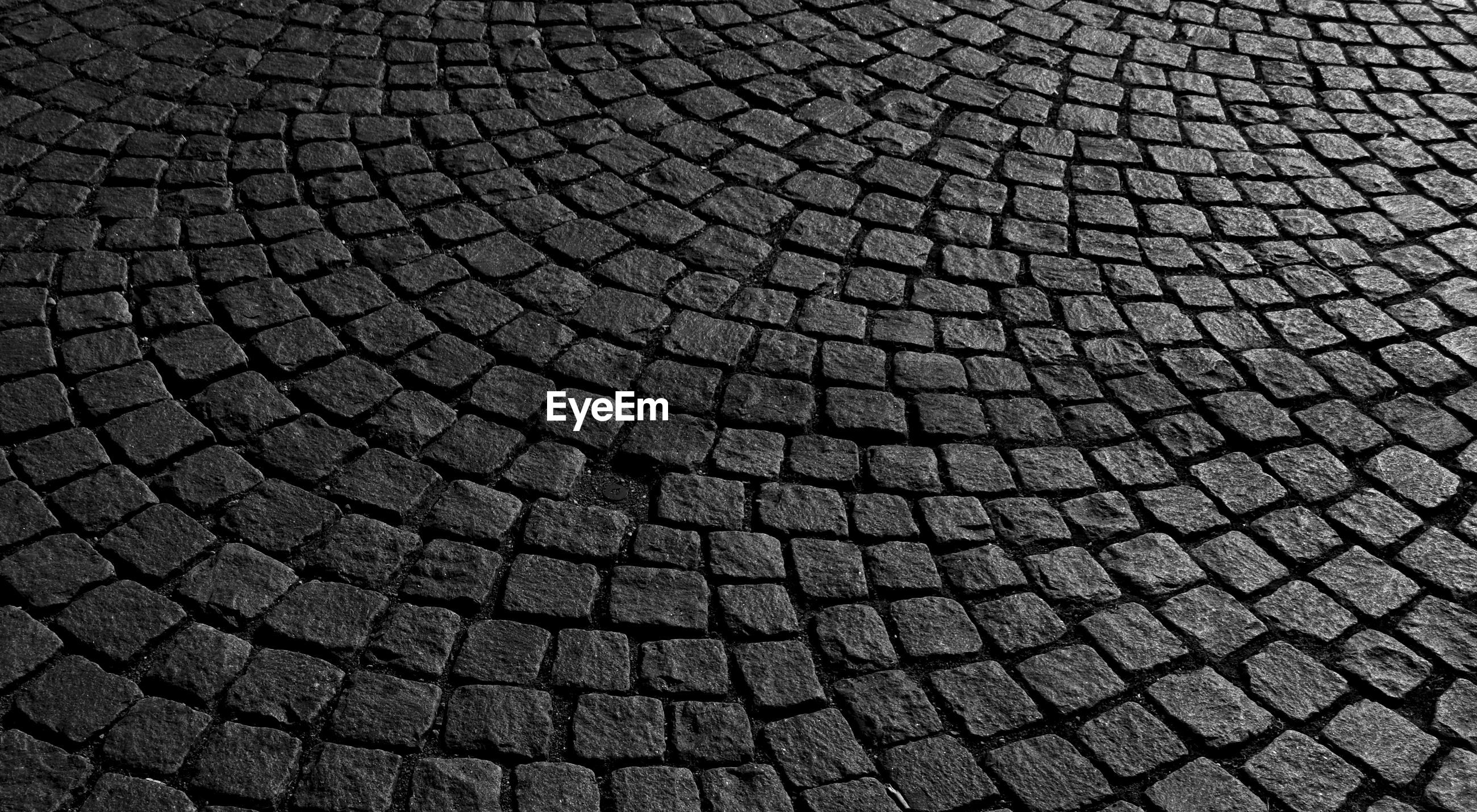 backgrounds, pattern, full frame, textured, cobblestone, no people, close-up, shape, street, repetition, design, geometric shape, outdoors, high angle view, city, day, gray, circle, black color, stone, concentric