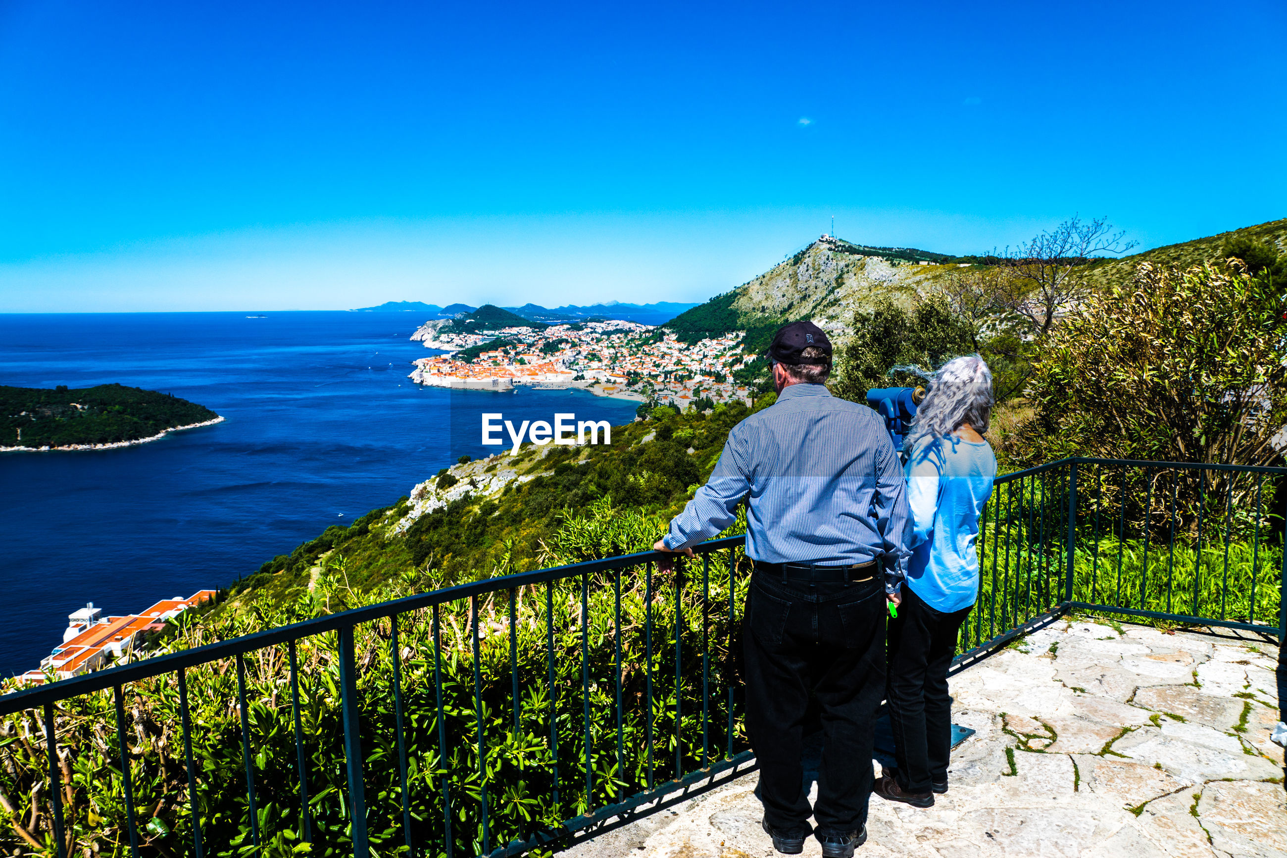 Full length rear view of senior couple standing by railing looking at sea against blue sky