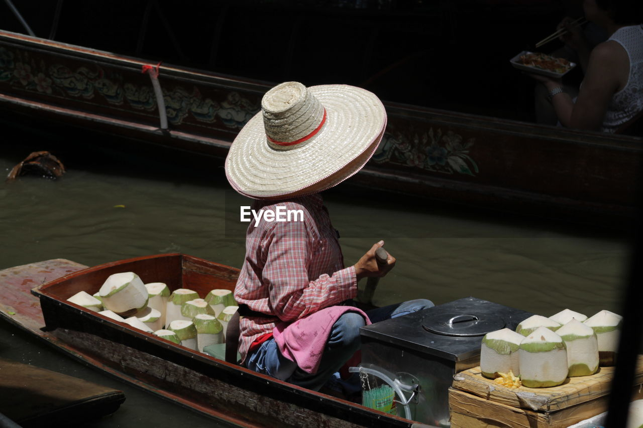 Man selling coconuts in boat at floating market