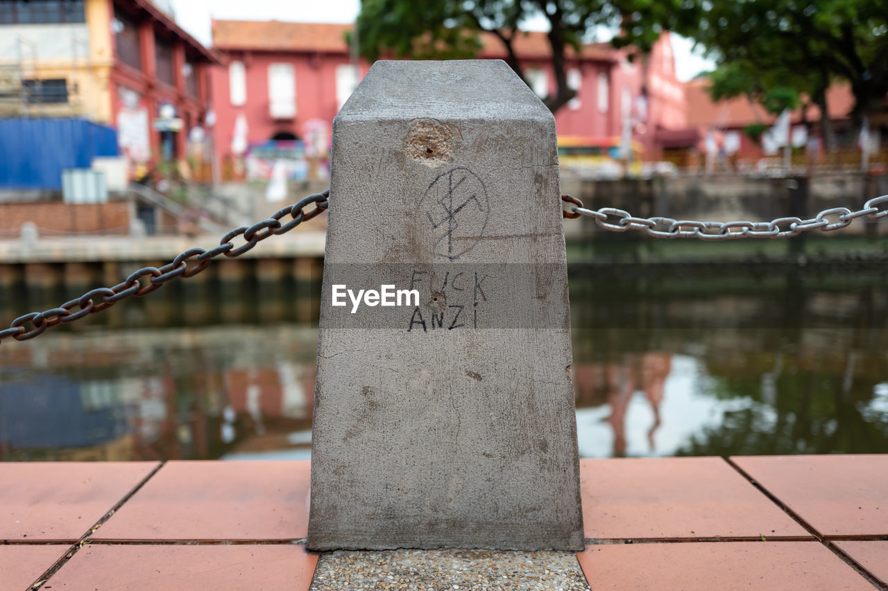 architecture, focus on foreground, water, text, built structure, day, communication, no people, western script, outdoors, building exterior, close-up, the past, nature, metal, history, building, city, script