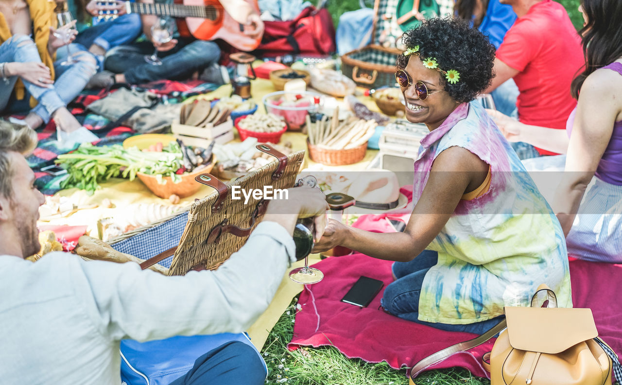 People Enjoying Food And Drink During Picnic