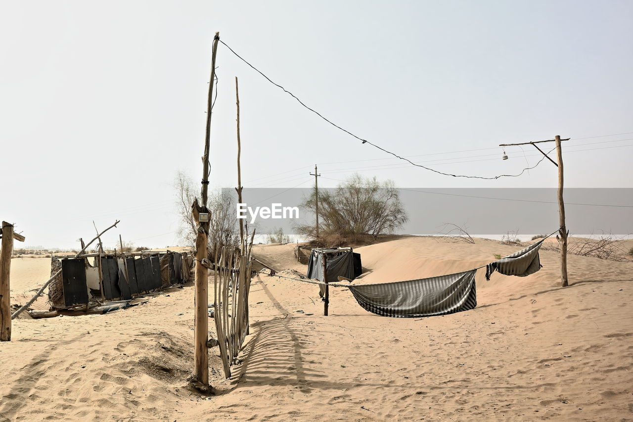 sky, land, sand, nature, clear sky, day, architecture, built structure, outdoors, beach, landscape, scenics - nature, building exterior, one person, desert, real people, tree, men, abandoned, arid climate
