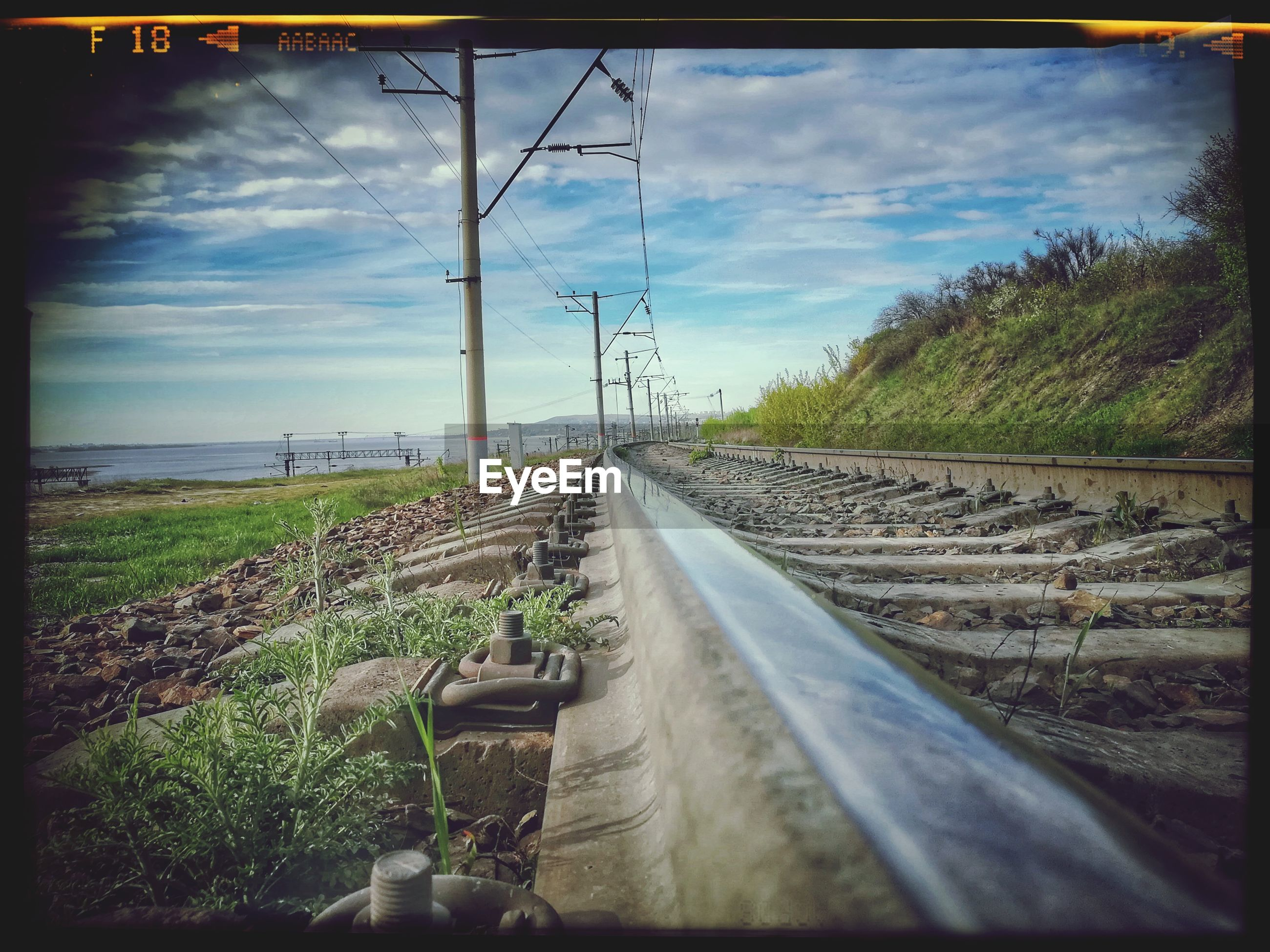 railroad track, transportation, rail transportation, sky, diminishing perspective, no people, the way forward, cloud - sky, railway track, day, landscape, cable, travel, public transportation, outdoors, grass, nature, electricity pylon, scenics, tree