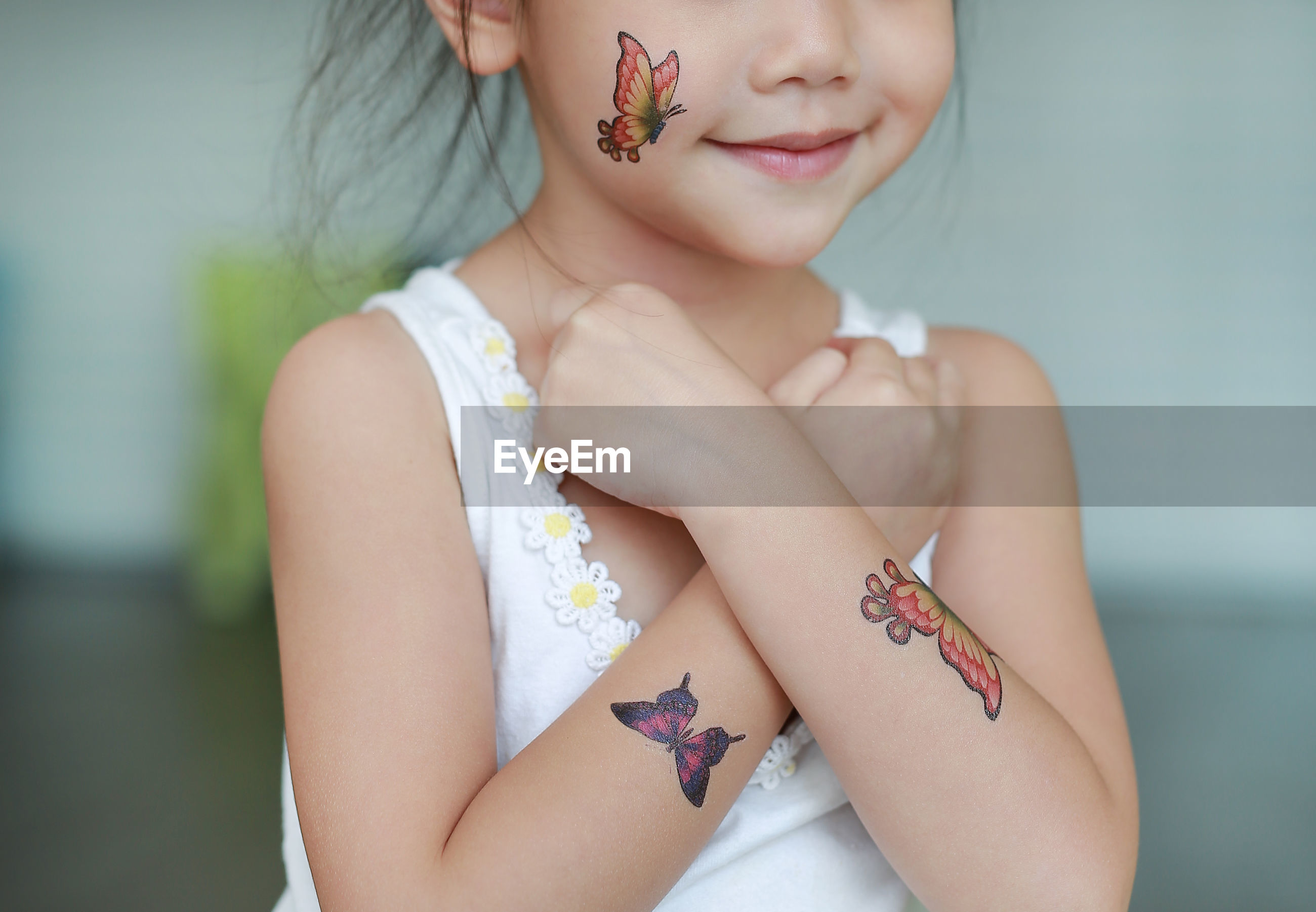Midsection of girl with artificial butterfly tattoos on body parts at home