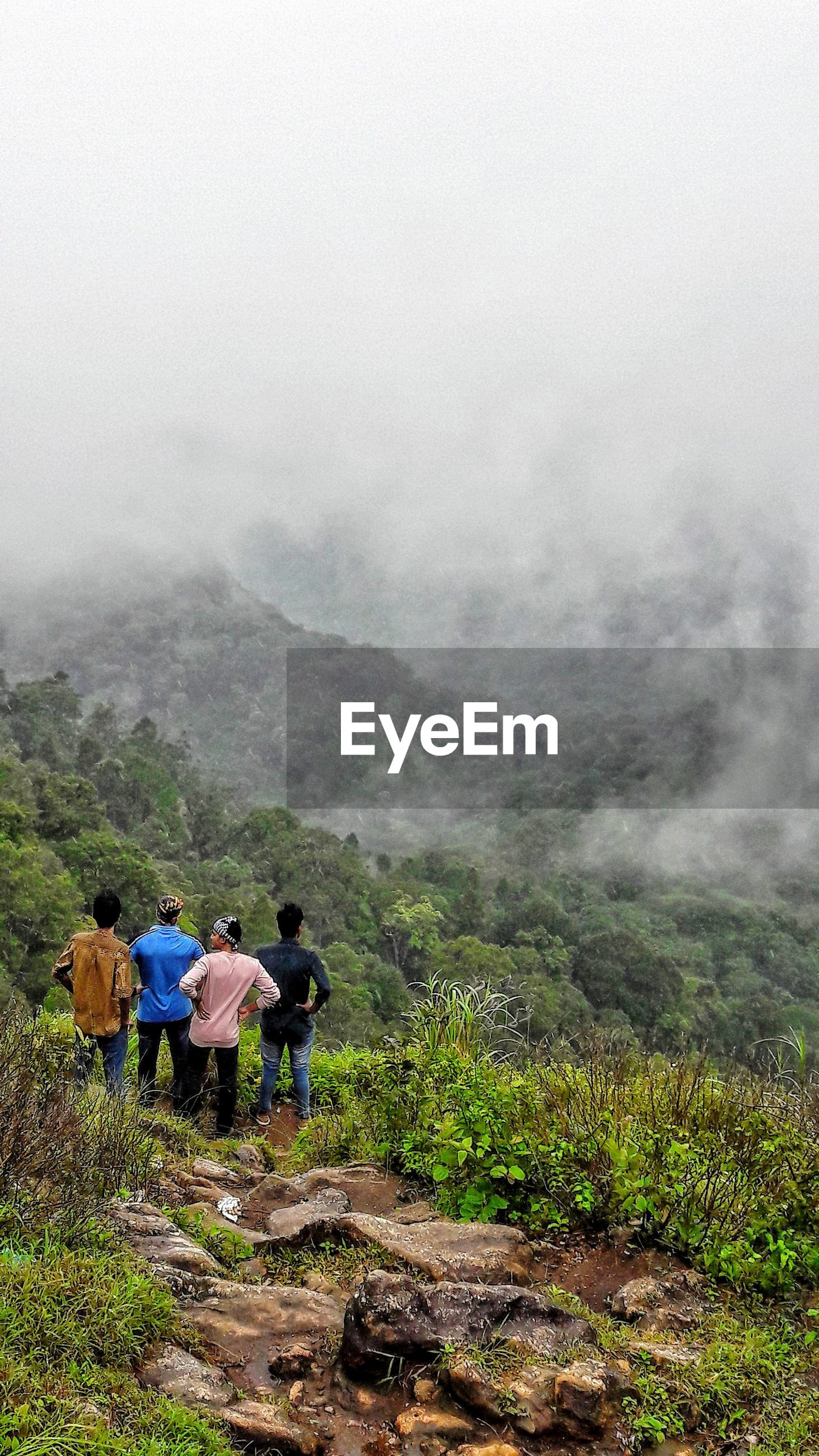 Friends looking at landscape while standing on mountain