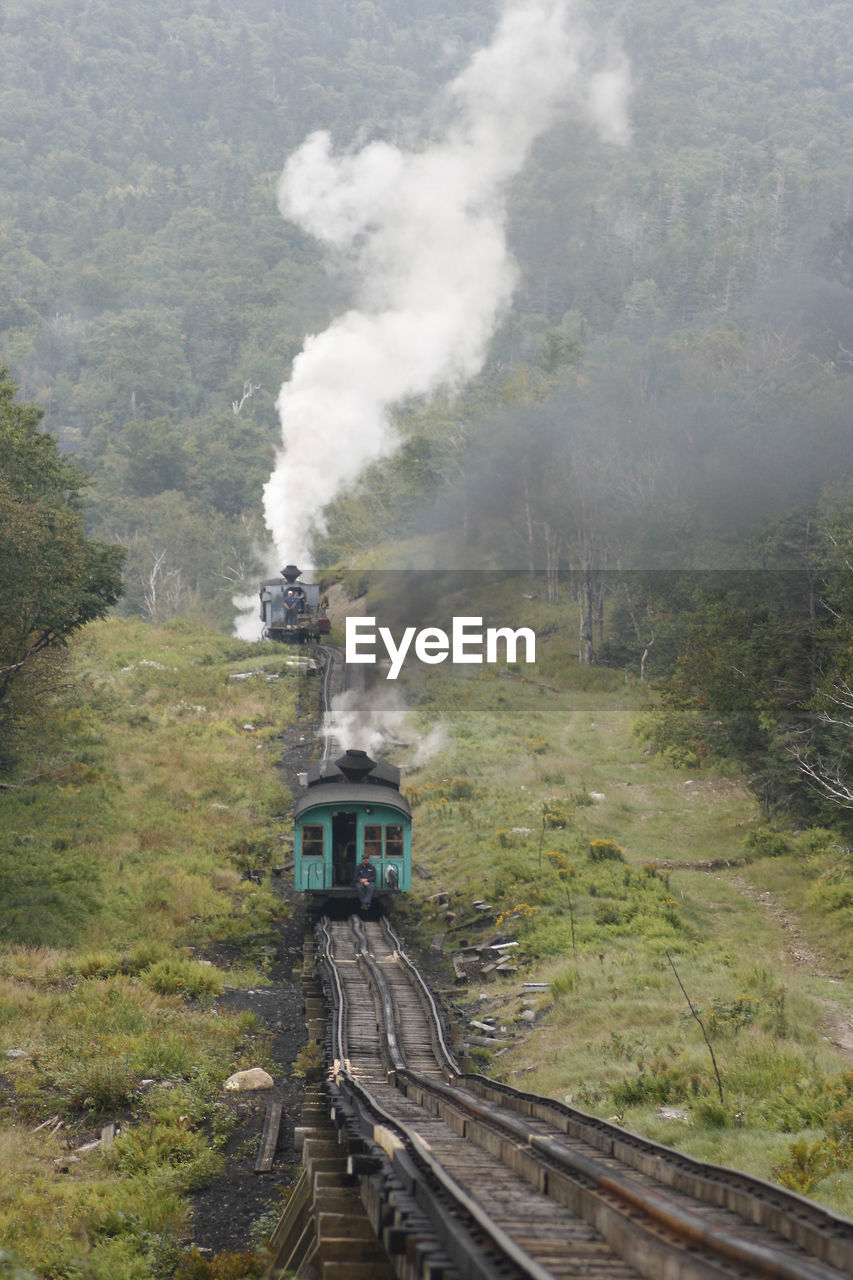 rail transportation, smoke - physical structure, train, train - vehicle, transportation, railroad track, tree, mode of transportation, track, public transportation, nature, plant, day, steam train, land, no people, mountain, environment, air pollution, pollution, outdoors