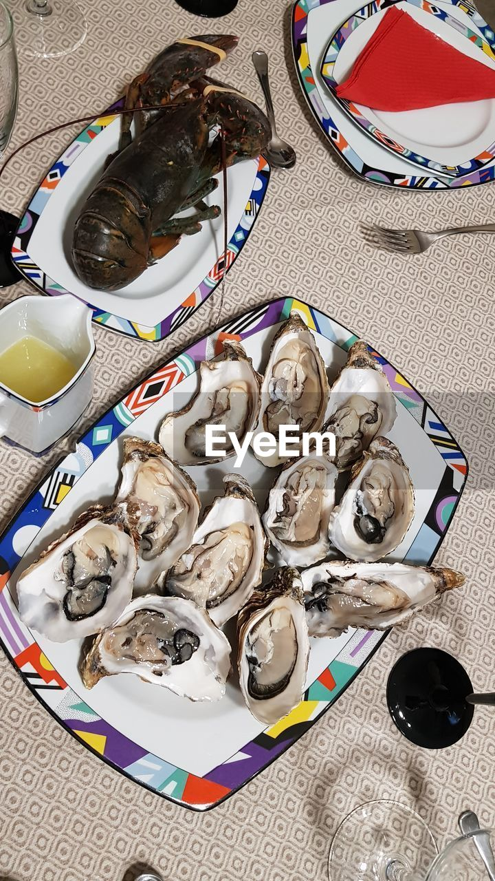 seafood, food and drink, food, animal, freshness, healthy eating, vertebrate, high angle view, table, plate, wellbeing, shell, fish, no people, raw food, still life, oyster, indoors, ready-to-eat, animal wildlife