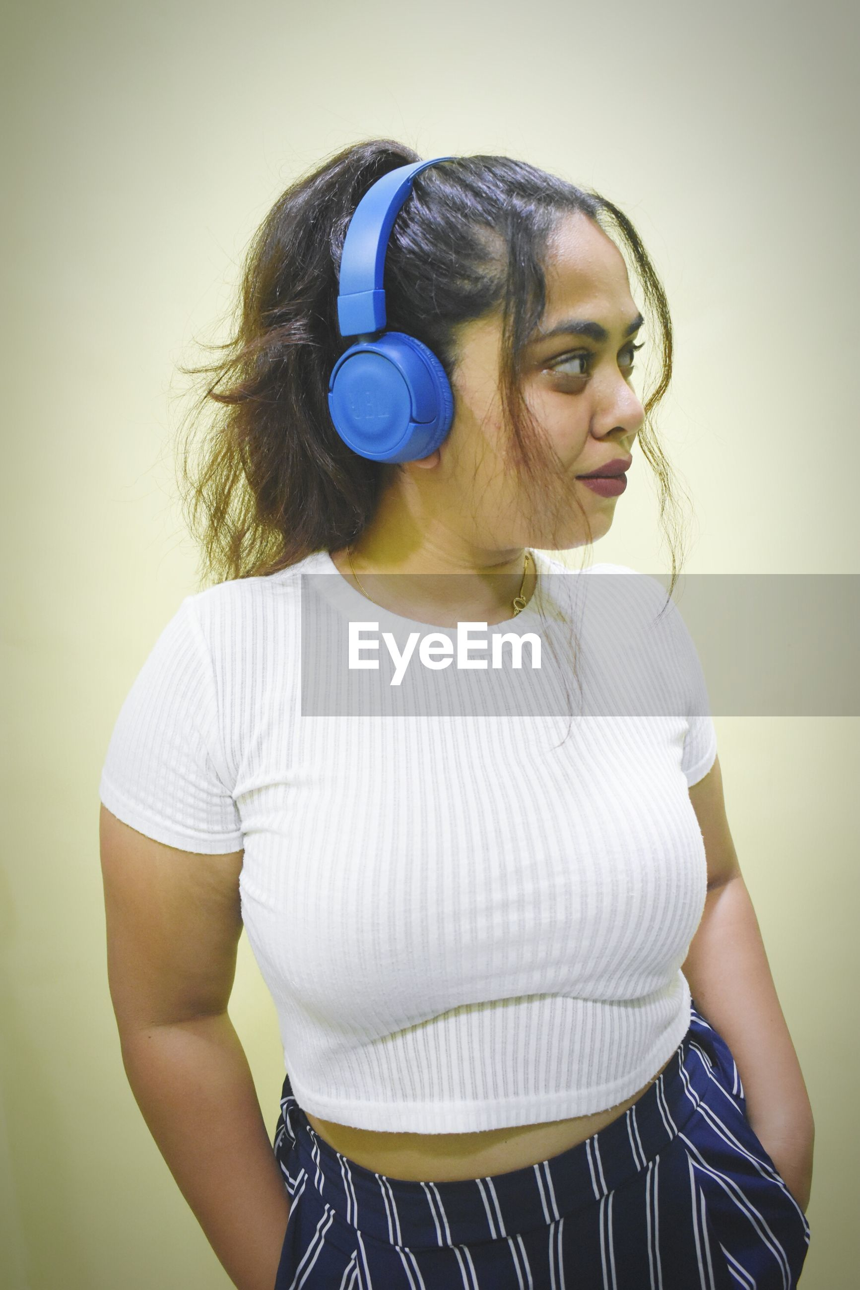 Young woman listening music over headphones standing against wall