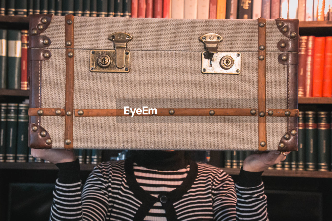Close-up of woman holding vintage suitcase by bookshelf