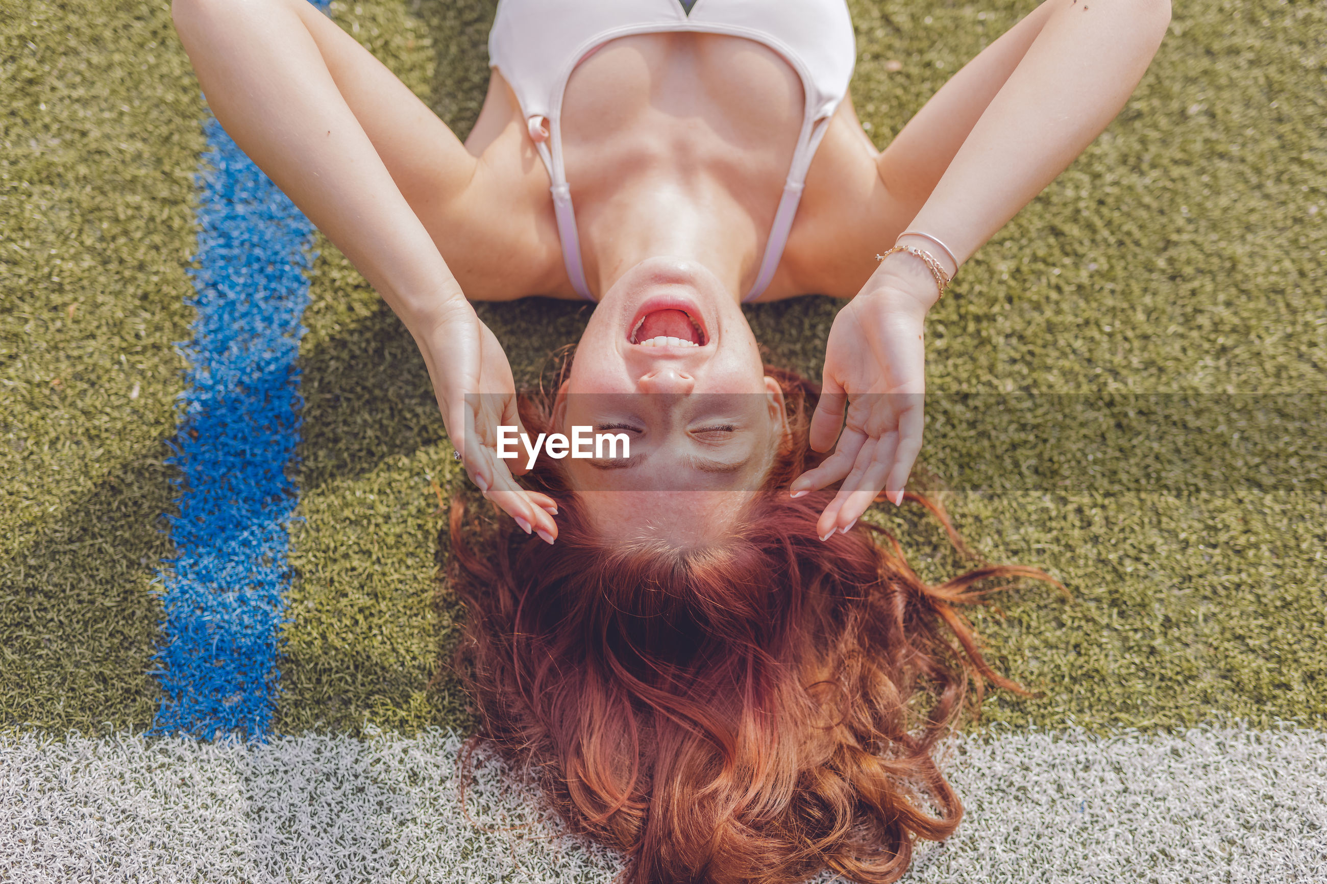 High angle view of young woman lying on field
