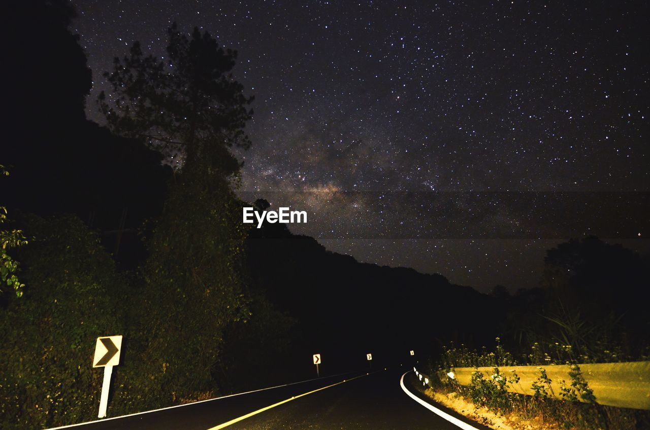 road, night, transportation, direction, sky, sign, space, scenics - nature, astronomy, nature, star - space, the way forward, galaxy, beauty in nature, no people, symbol, star field, star, infinity, tranquil scene, guidance, outdoors, diminishing perspective, milky way