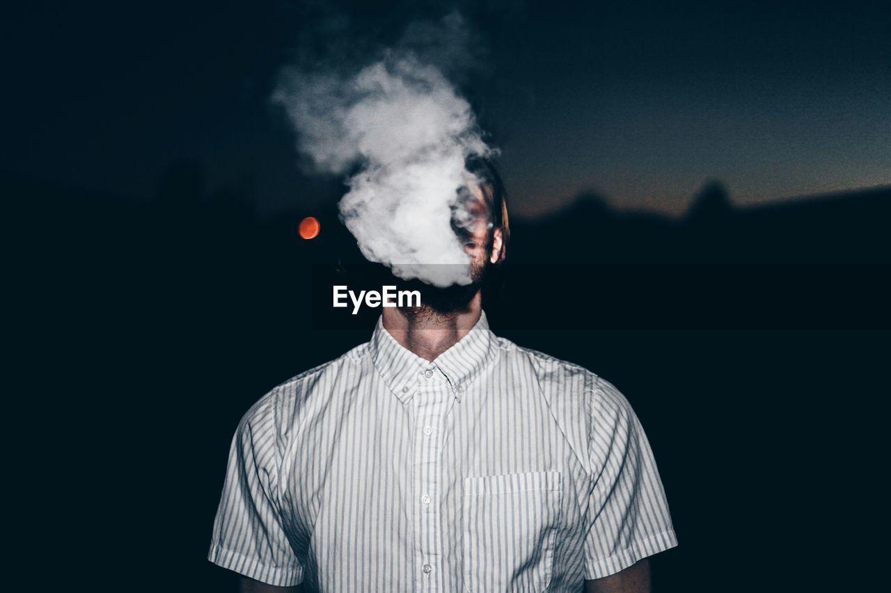 Man Smoking Against Blurred Background