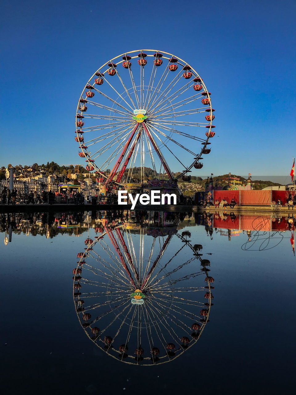 reflection, water, ferris wheel, blue, clear sky, sky, amusement park, built structure, waterfront, architecture, building exterior, outdoors, day, no people