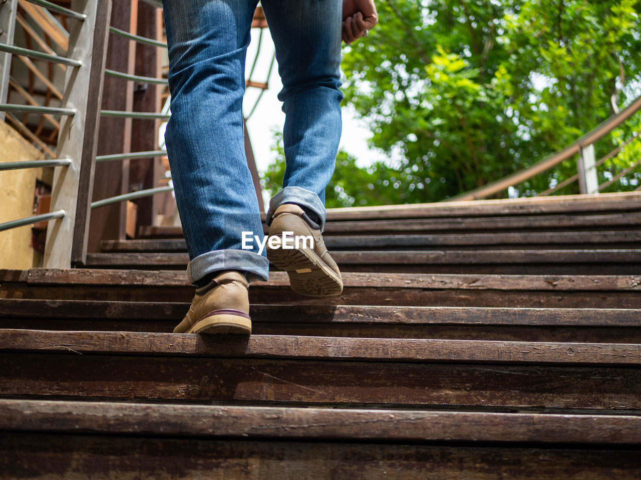 low section, human leg, staircase, architecture, one person, human body part, men, jeans, body part, real people, casual clothing, shoe, day, railing, moving up, steps and staircases, low angle view, lifestyles, leisure activity, outdoors, human foot, human limb