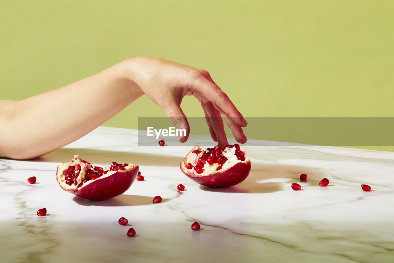 food, food and drink, human hand, one person, hand, red, fruit, healthy eating, freshness, wellbeing, human body part, indoors, pomegranate, body part, women, real people, lifestyles, adult, pomegranate seed, human limb, finger, temptation