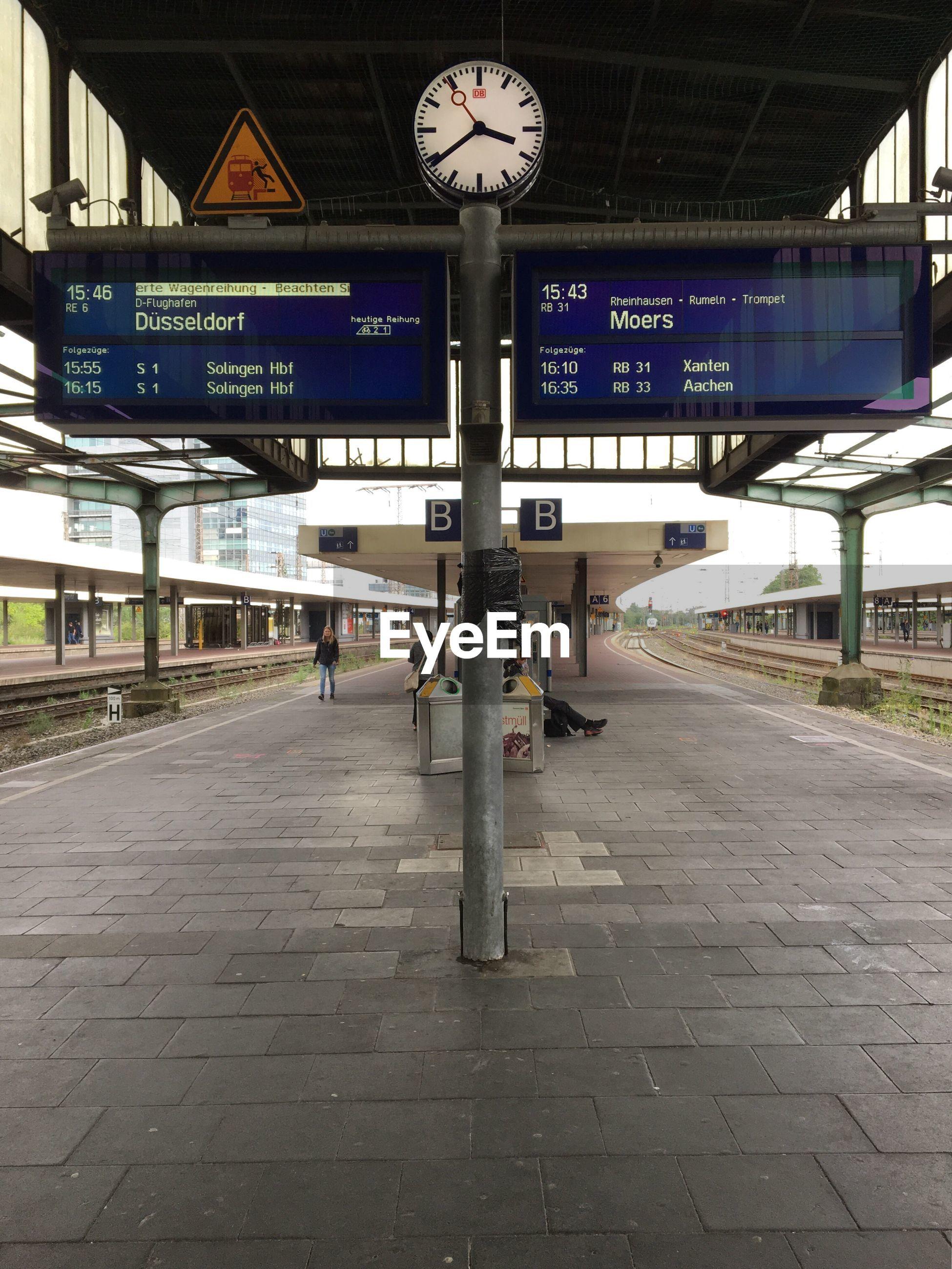 Clock and arrival departure boards on railroad station platform