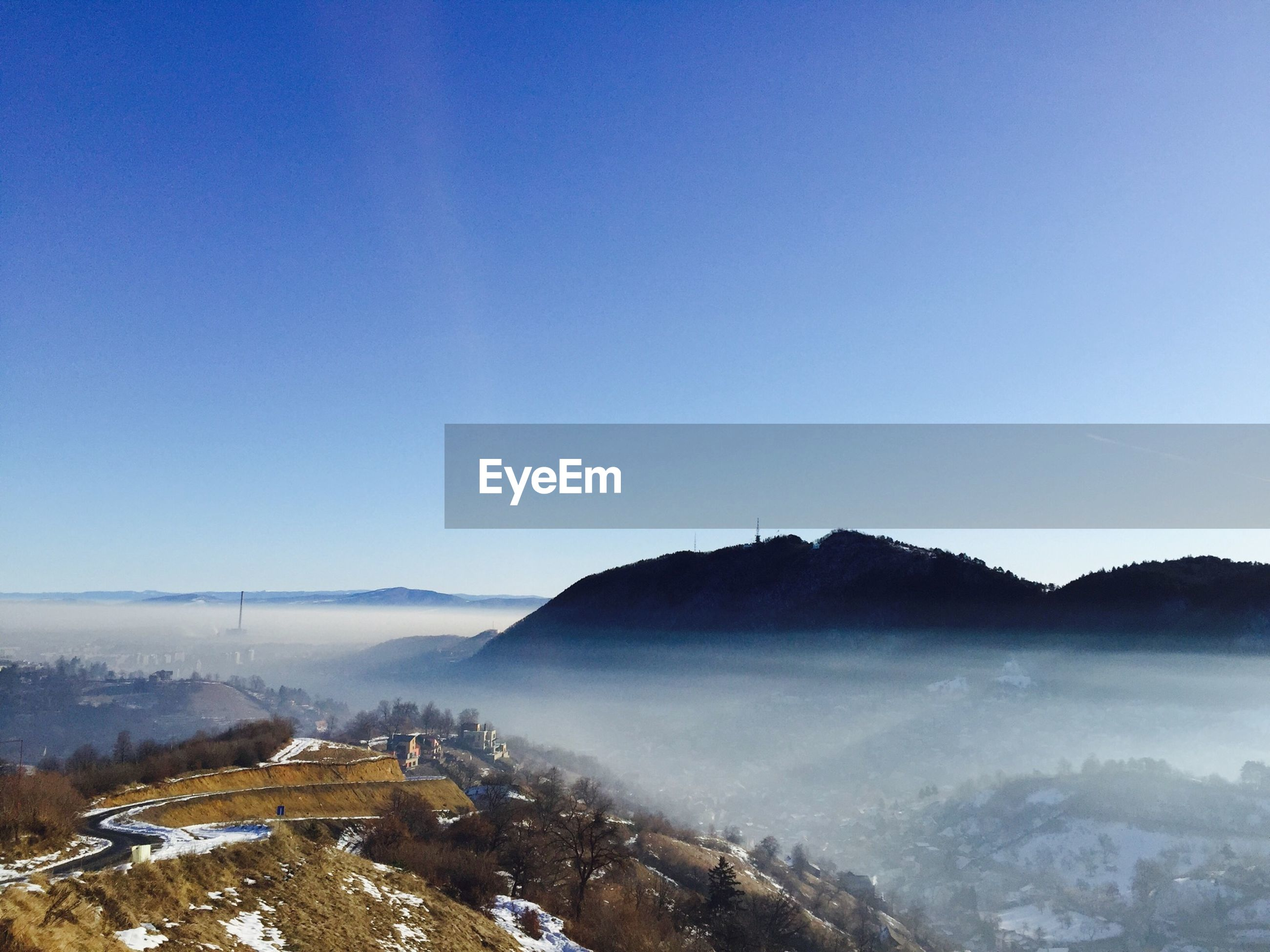 High angle view of mountains in foggy weather against clear blue sky