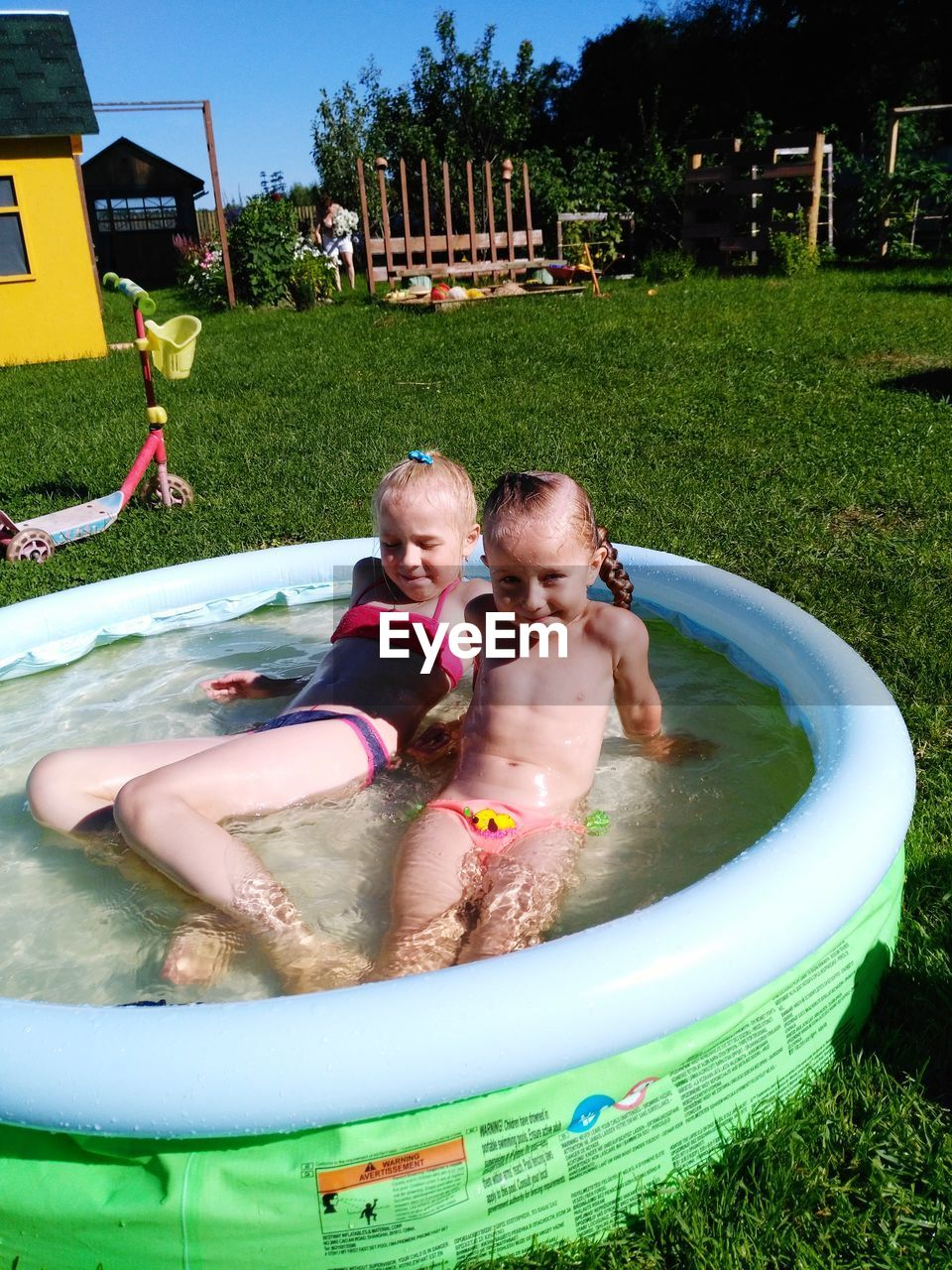Siblings Swimming In Wading Pool