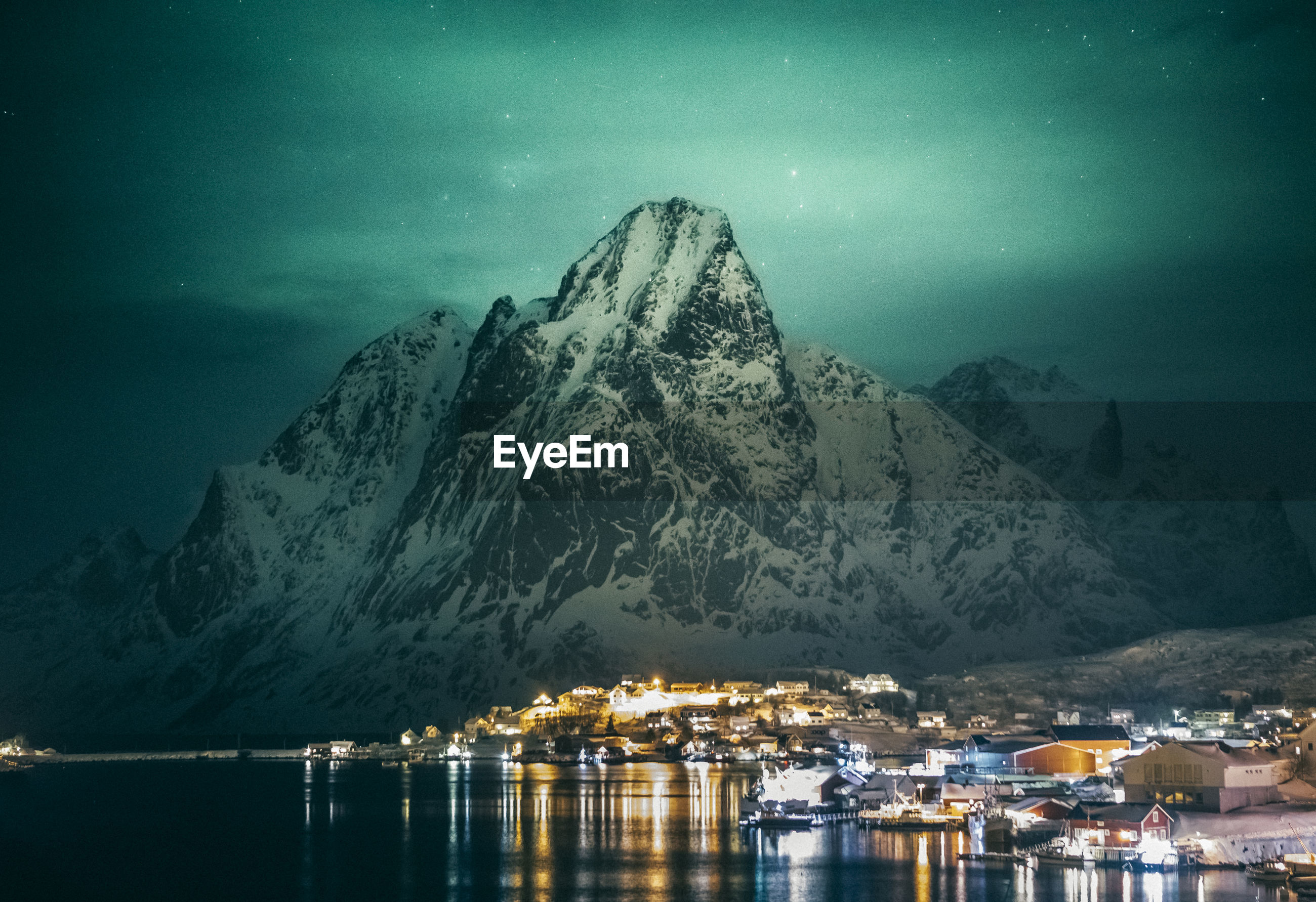 Scenic view of sea by snowcapped mountains against sky at night