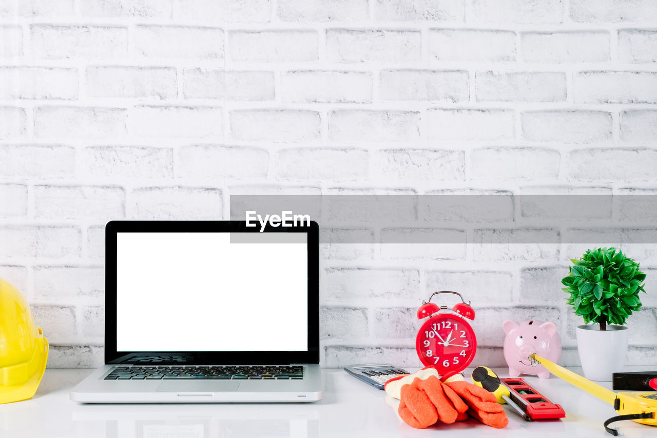technology, computer, wireless technology, laptop, copy space, connection, communication, indoors, table, white color, brick wall, no people, brick, wall - building feature, wall, still life, black color, computer equipment, cup, using laptop, surfing the net