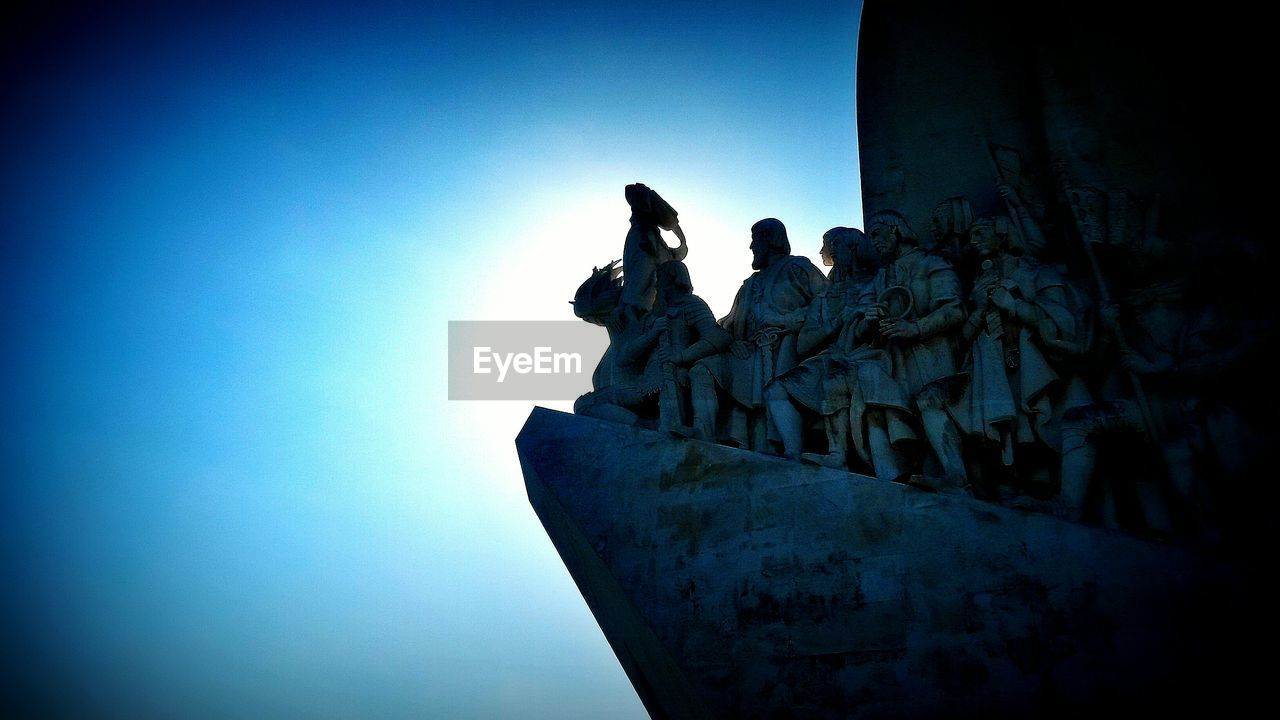 Low angle view of monument to the discoveries against clear blue sky on sunny day
