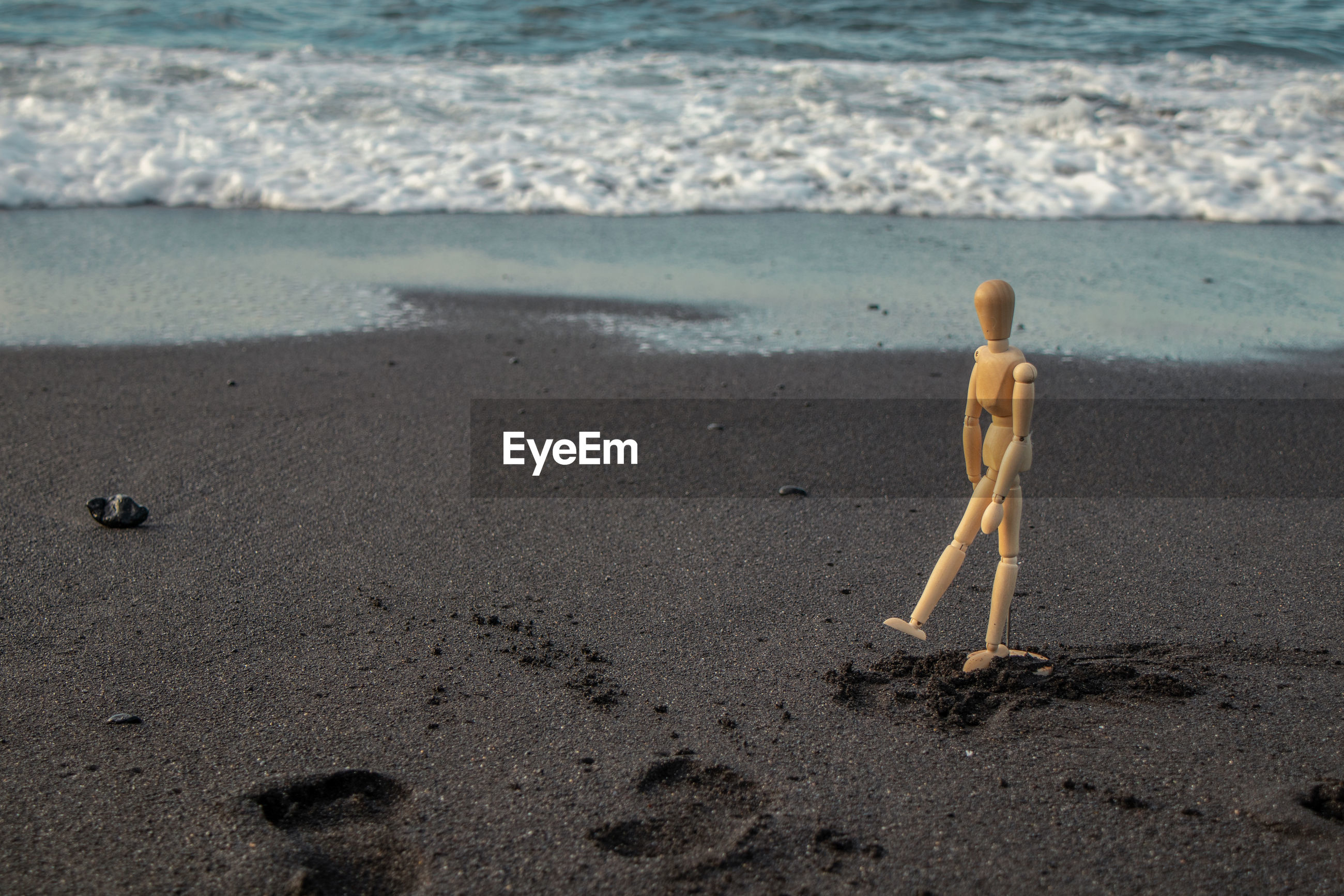 A wooden dummy walks along the beach with black sand