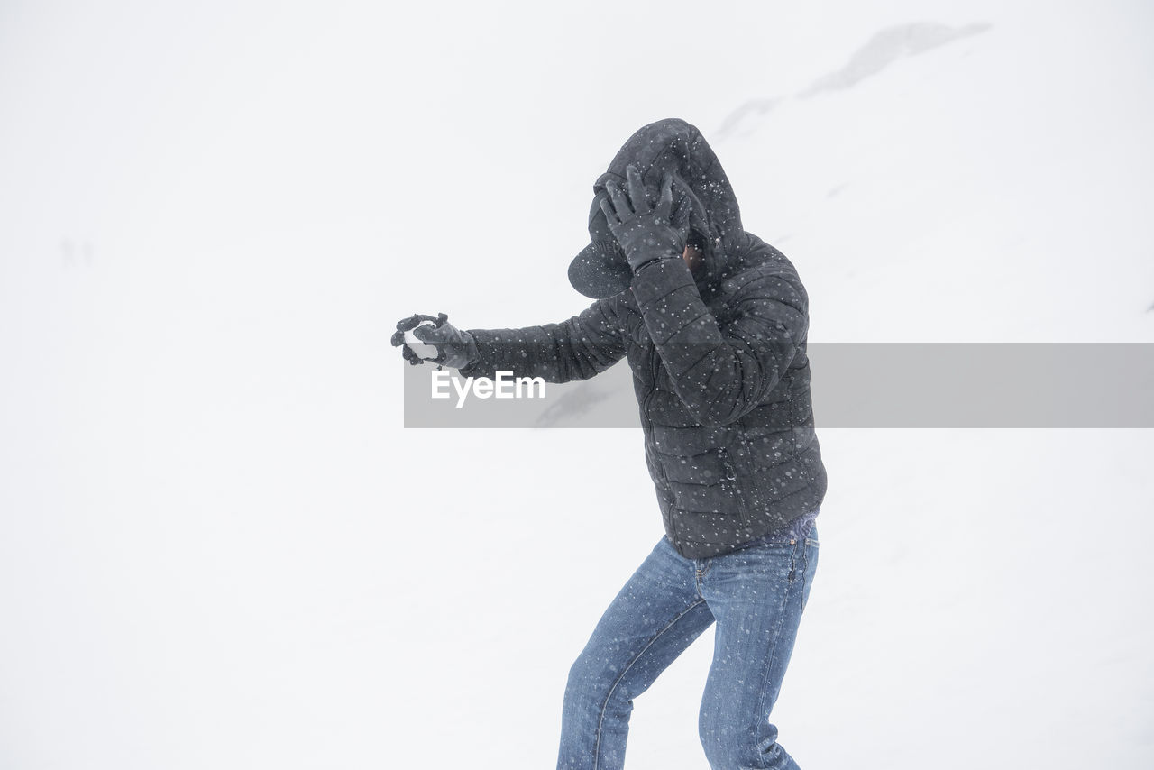 Man Wearing Warm Clothing While Standing On Snowy Field During Snowfall