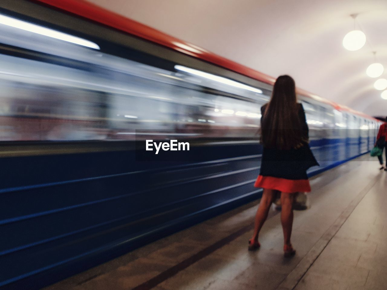 Rear view full length of woman standing by blurred motion of train at railroad station