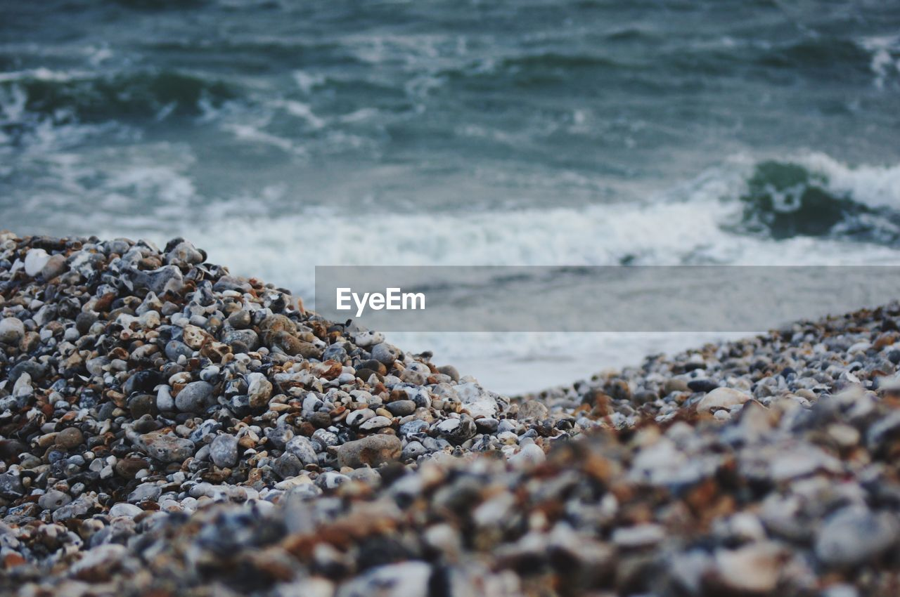 sea, water, beach, rock, solid, wave, motion, no people, stone - object, land, stone, pebble, selective focus, rock - object, nature, day, aquatic sport, sport, beauty in nature, outdoors, surface level