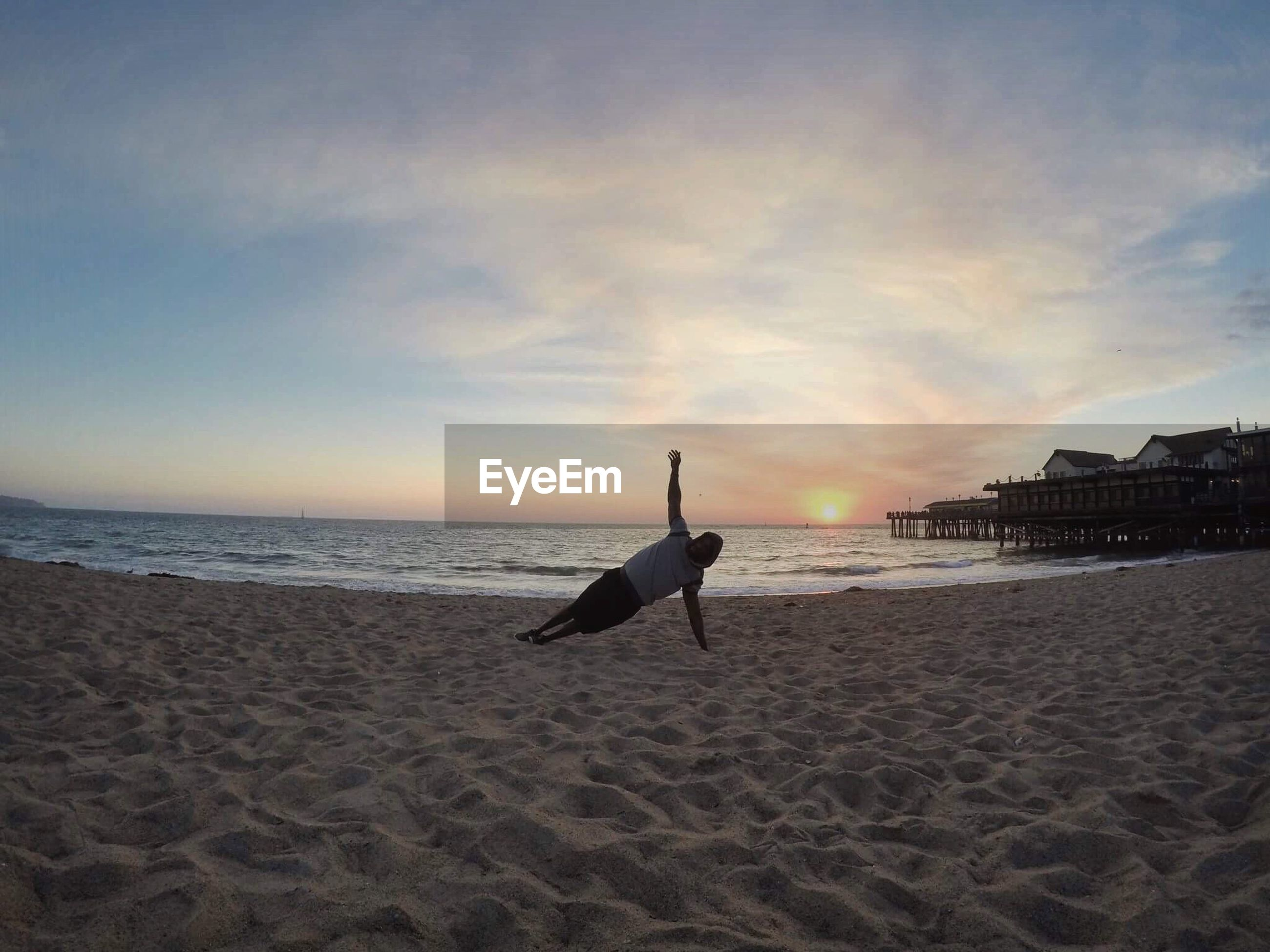 Full length of man exercising at beach against sky during sunset