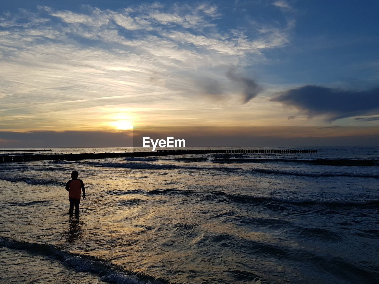 sky, water, sea, sunset, beach, beauty in nature, land, horizon over water, scenics - nature, real people, cloud - sky, horizon, lifestyles, one person, motion, men, leisure activity, nature, outdoors