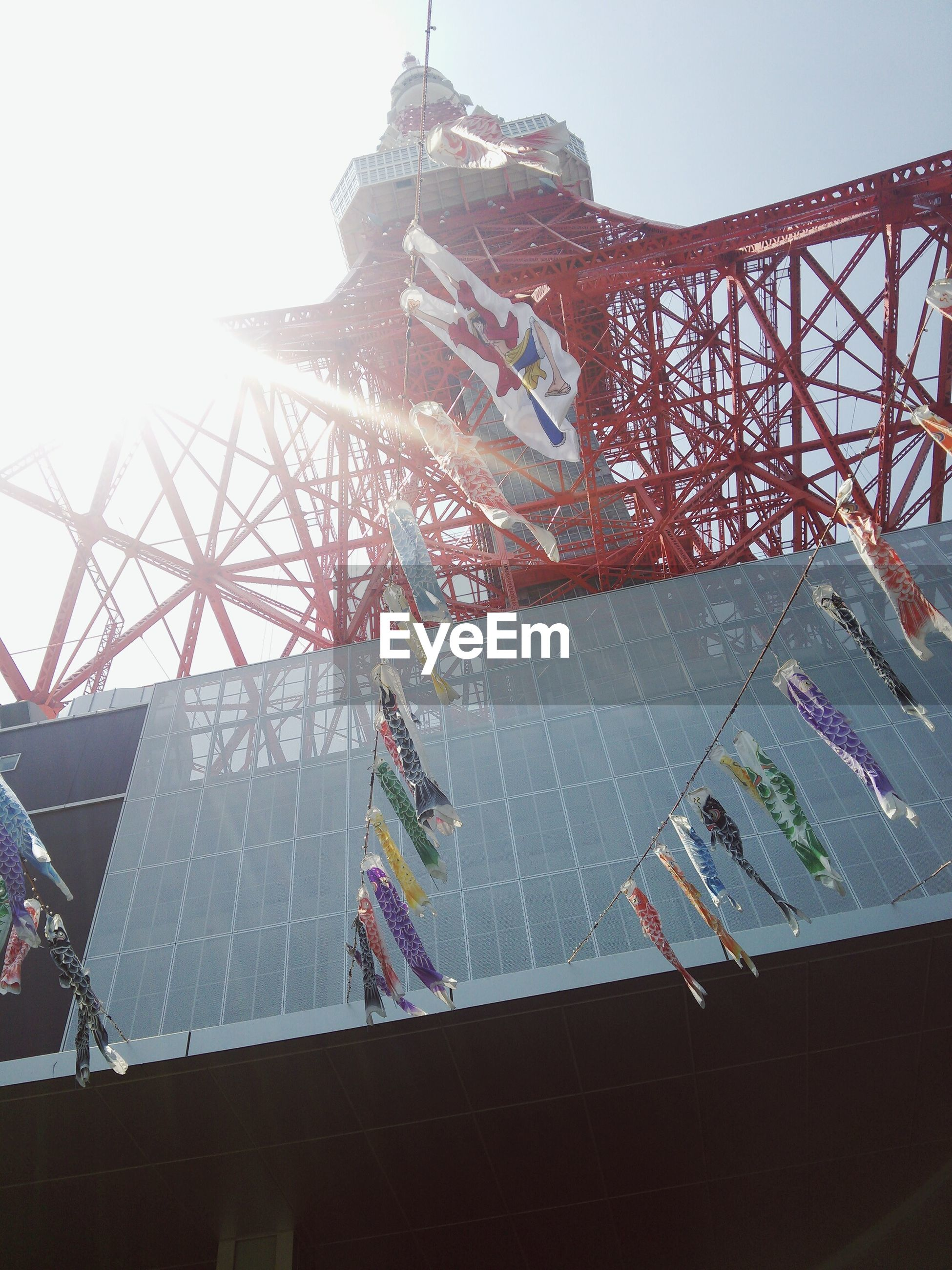 low angle view, amusement park, amusement park ride, clear sky, built structure, sky, arts culture and entertainment, architecture, day, fun, building exterior, outdoors, sunlight, metal, ferris wheel, leisure activity, enjoyment, city, tradition