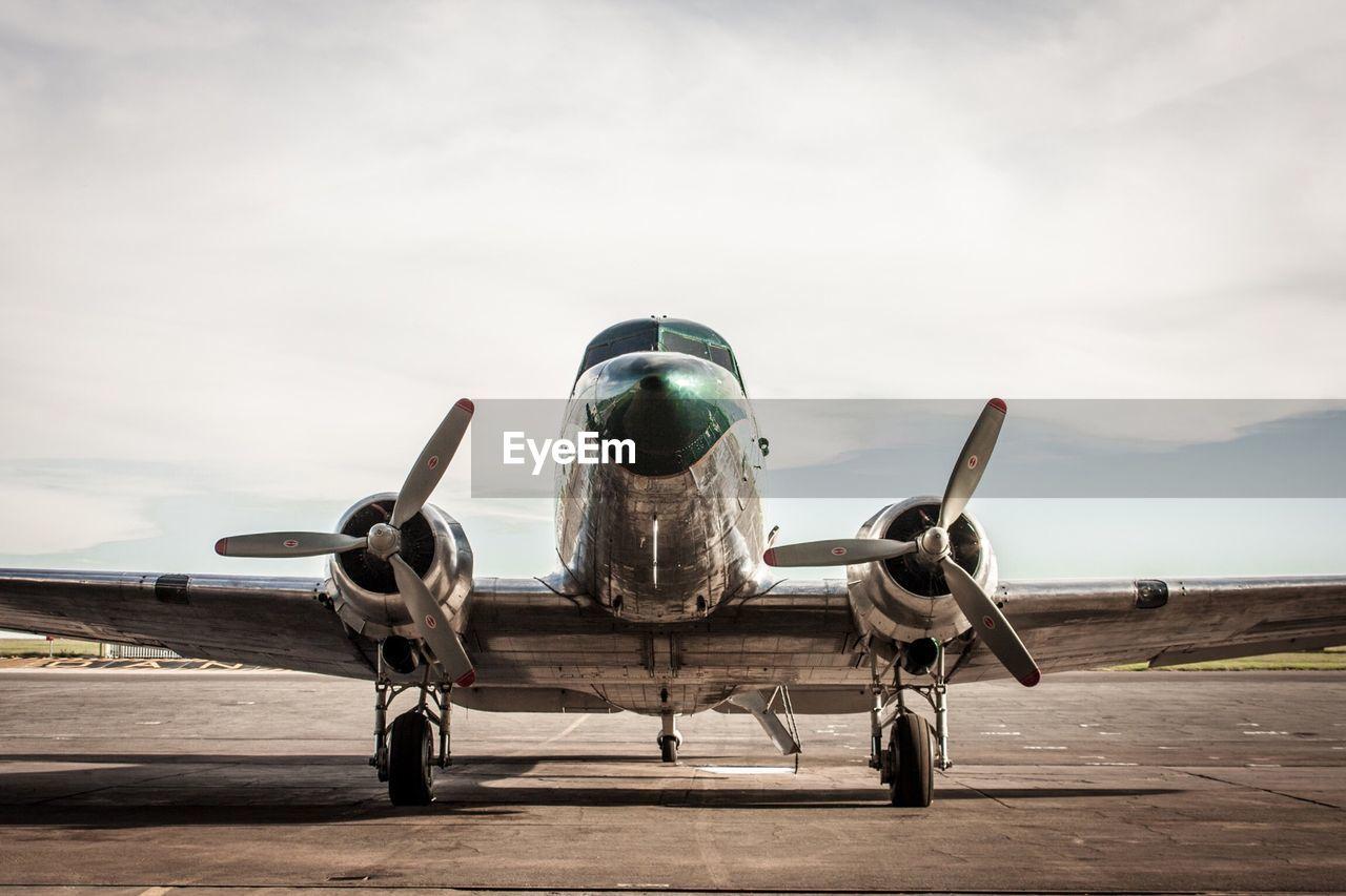 Douglas dc-3 on runway against cloudy sky