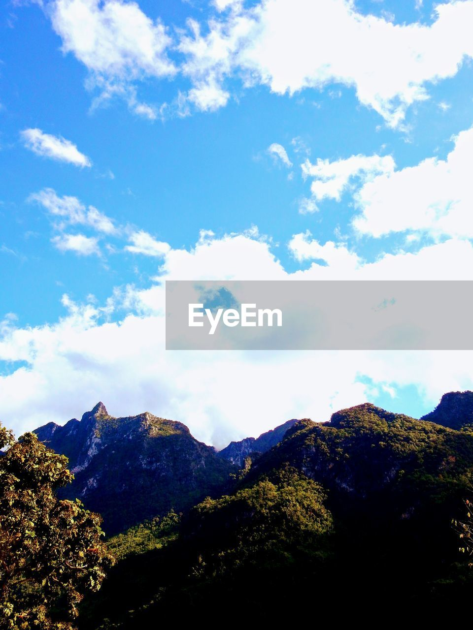 mountain, beauty in nature, tranquility, scenics, tranquil scene, nature, sky, day, outdoors, no people, mountain range, cloud - sky, low angle view, blue, landscape, tree