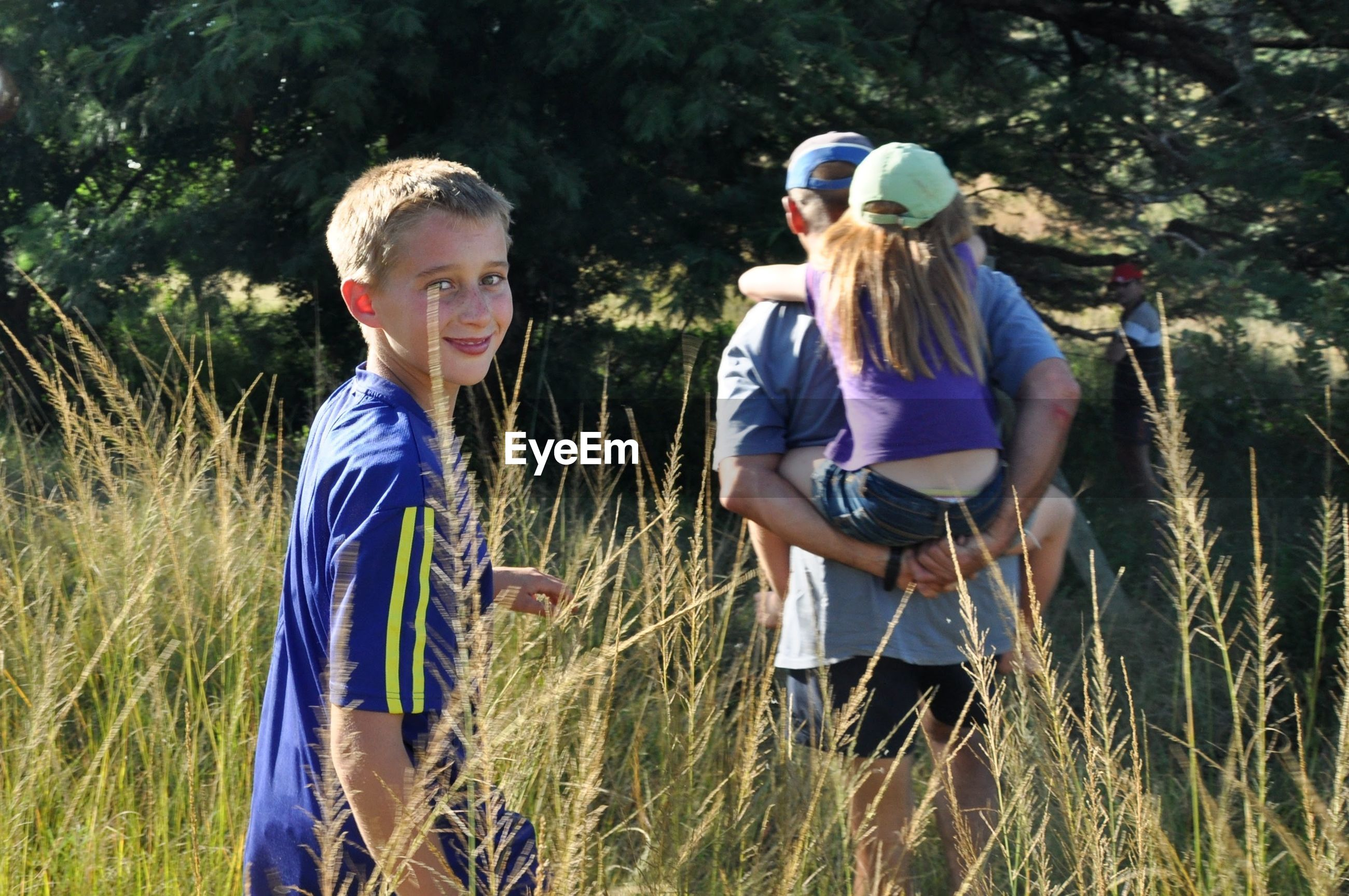 Portrait of happy boy walking with father giving piggyback sister in grassy forest