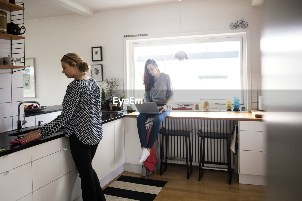 WOMAN STANDING ON TABLE BY WINDOW IN KITCHEN