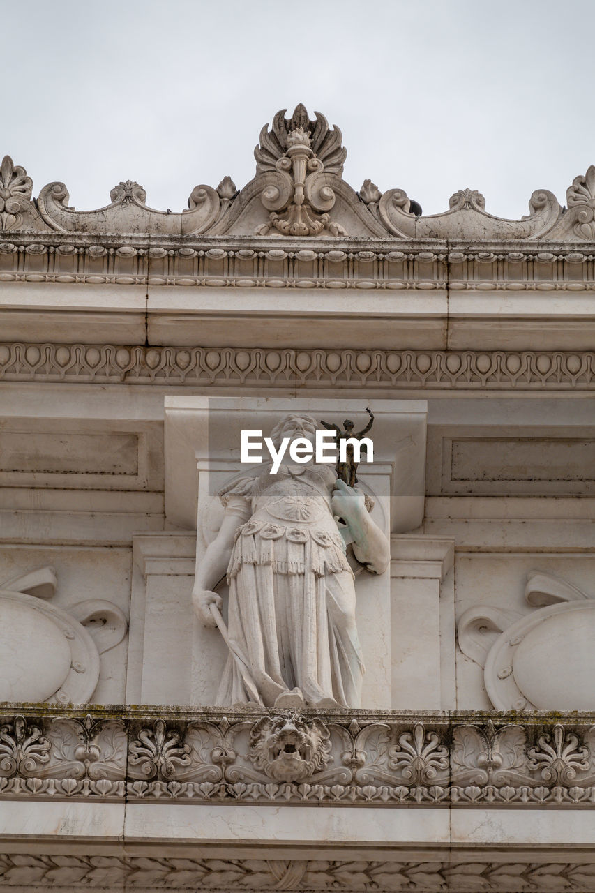 representation, human representation, sculpture, art and craft, statue, architecture, male likeness, creativity, craft, built structure, female likeness, building exterior, history, travel destinations, the past, low angle view, carving - craft product, no people, day, sky, ornate