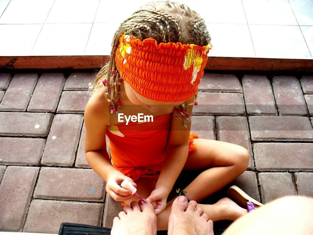 High Angle View Of Girl Applying Nail Polish On Mother Toenail