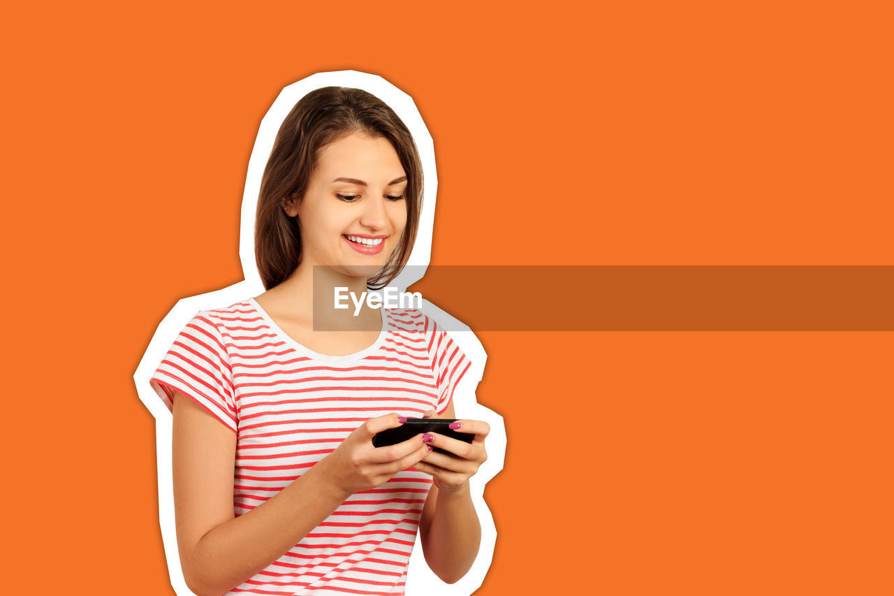 Digital composite image of smiling young woman using smart phone against orange background