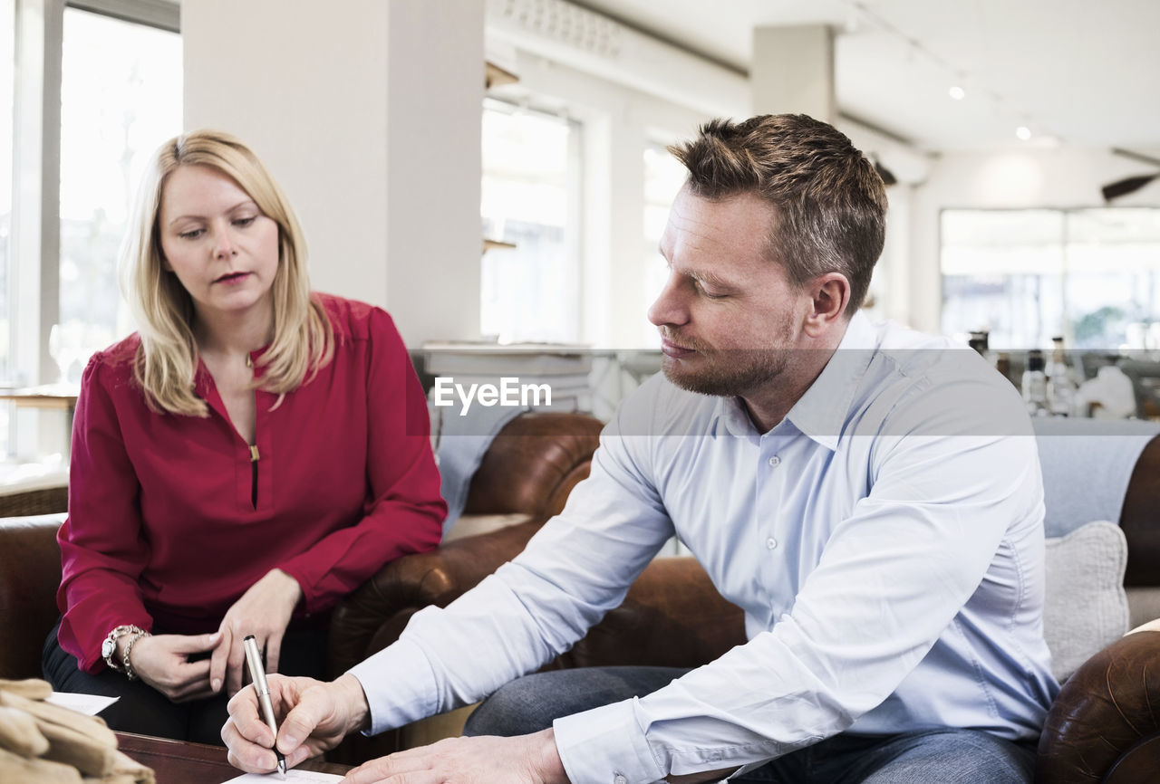 YOUNG COUPLE SITTING IN A ROOM