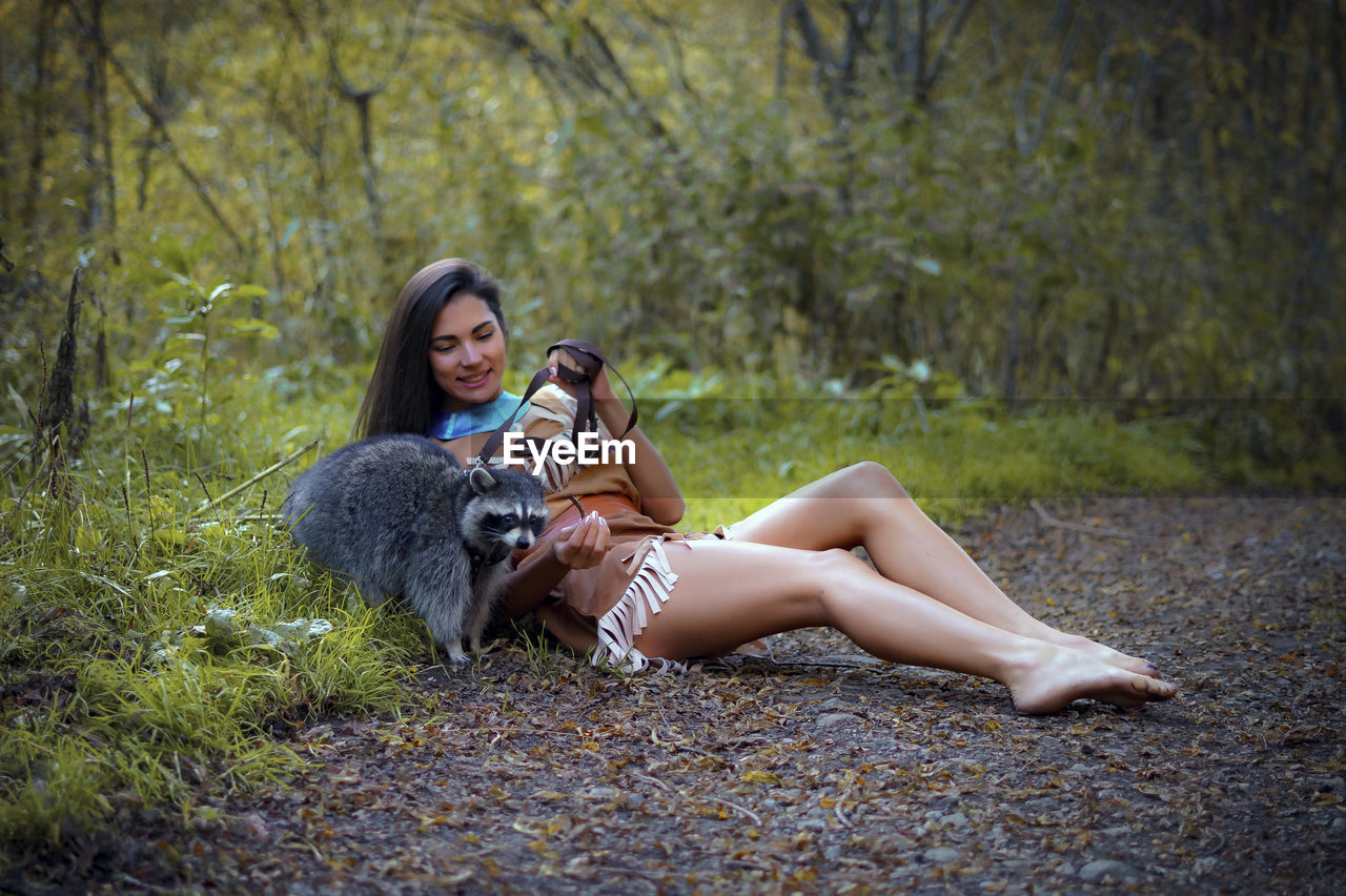Smiling Young Woman In Traditional Clothing Sitting By Raccoon In Forest