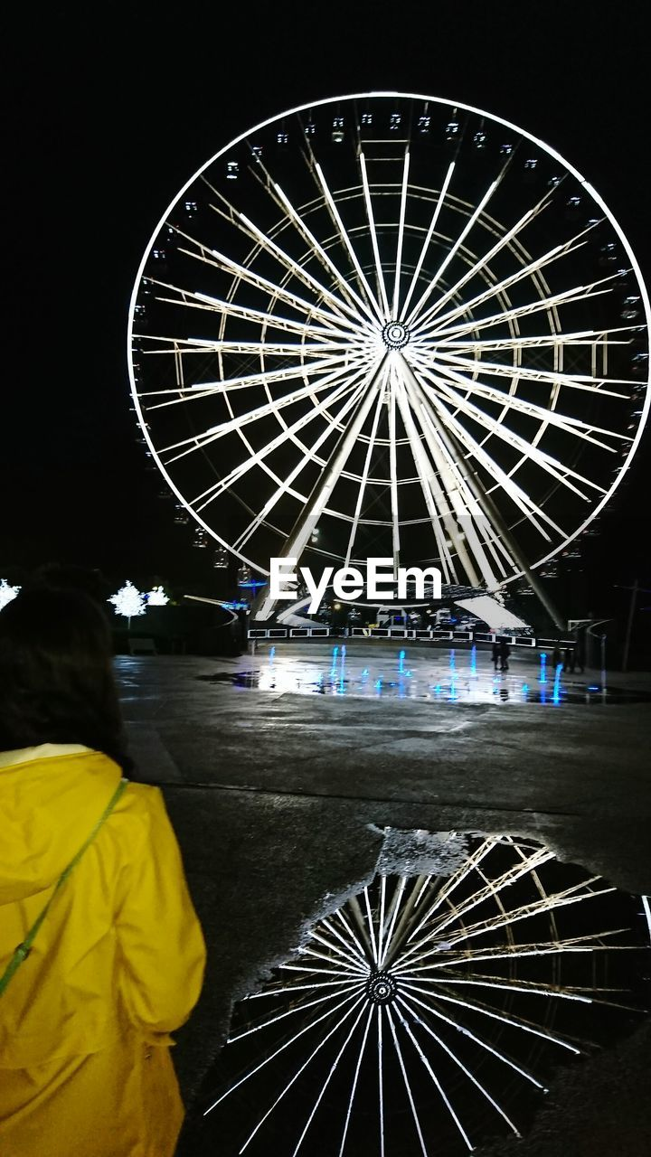 night, rear view, arts culture and entertainment, real people, illuminated, amusement park, men, ferris wheel, amusement park ride, leisure activity, lifestyles, women, standing, one person, outdoors, people