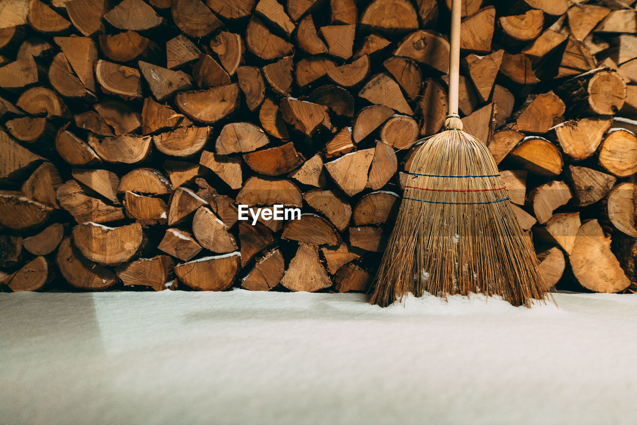 Broom And Firewood By Snow