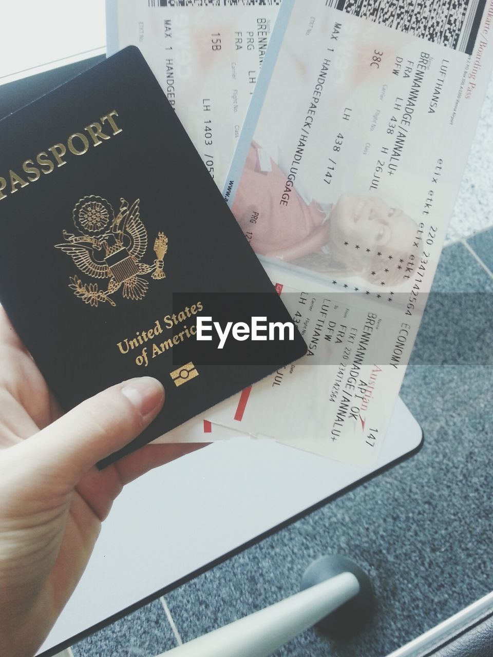 holding, passport, travel, text, real people, high angle view, indoors, one person, close-up, human hand, vacations, airplane, day, people