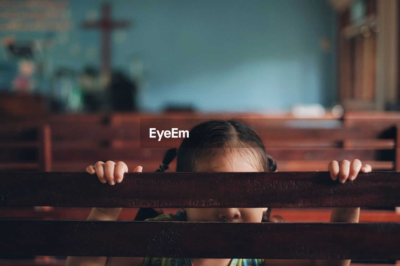 Girl Hiding Behind Pew In Church